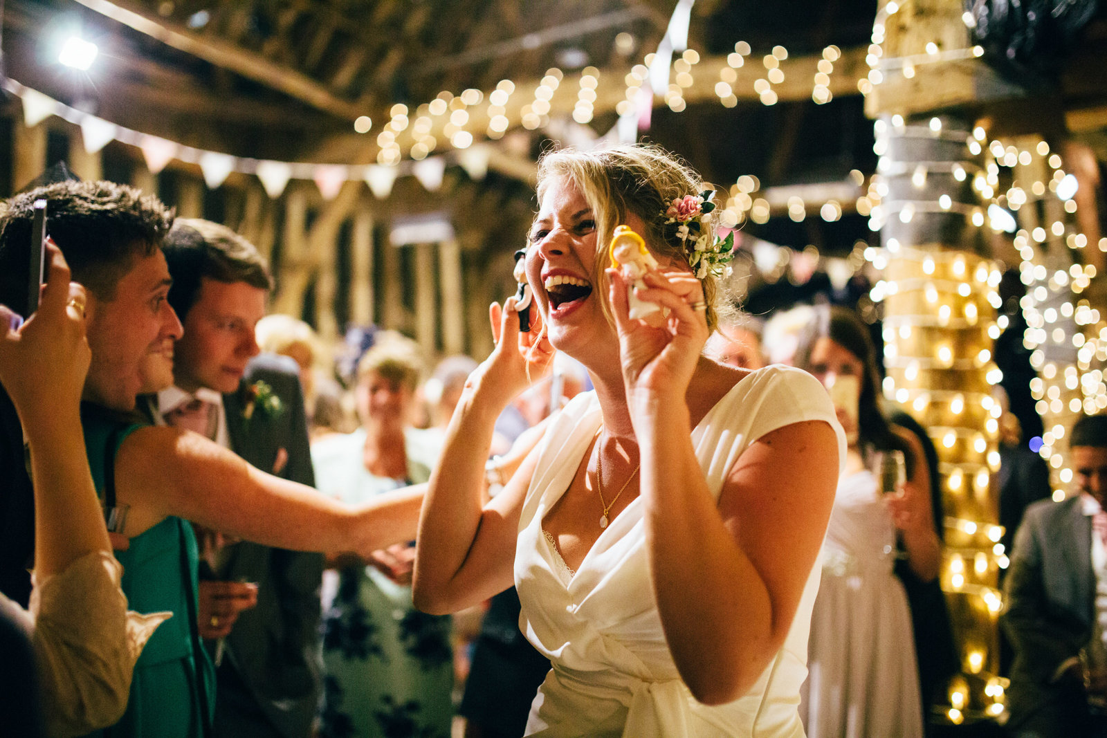 Bride laughing amongst fairy lights with her wedding cake toppers at Blackthorpe Bar