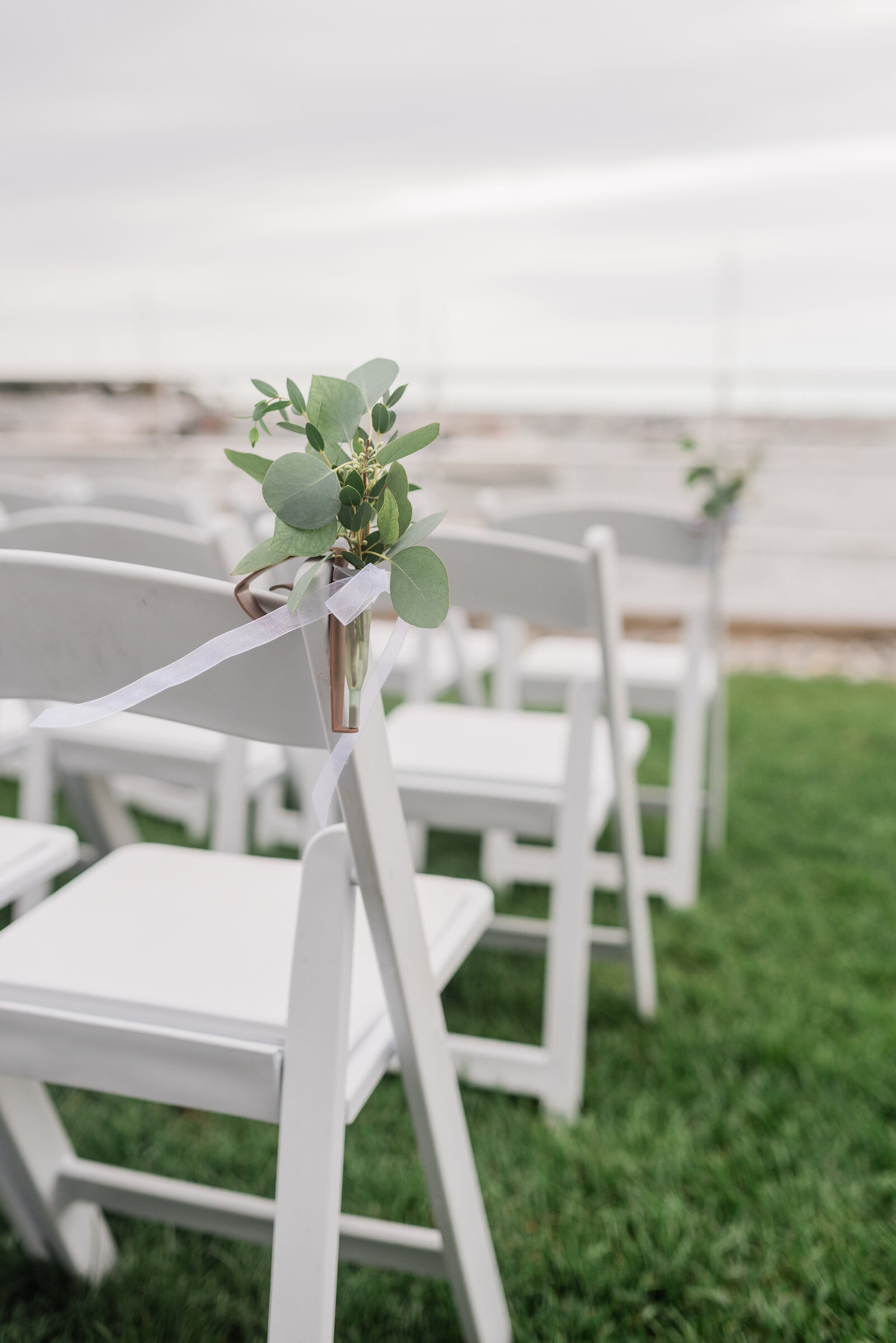 Ceremony chairs set up on the lawn with florals at the Duxbury Bay Maritime School