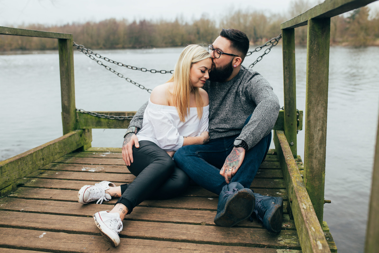 Photo of relaxed couple sitting and  cuddling by the water in Ipswich