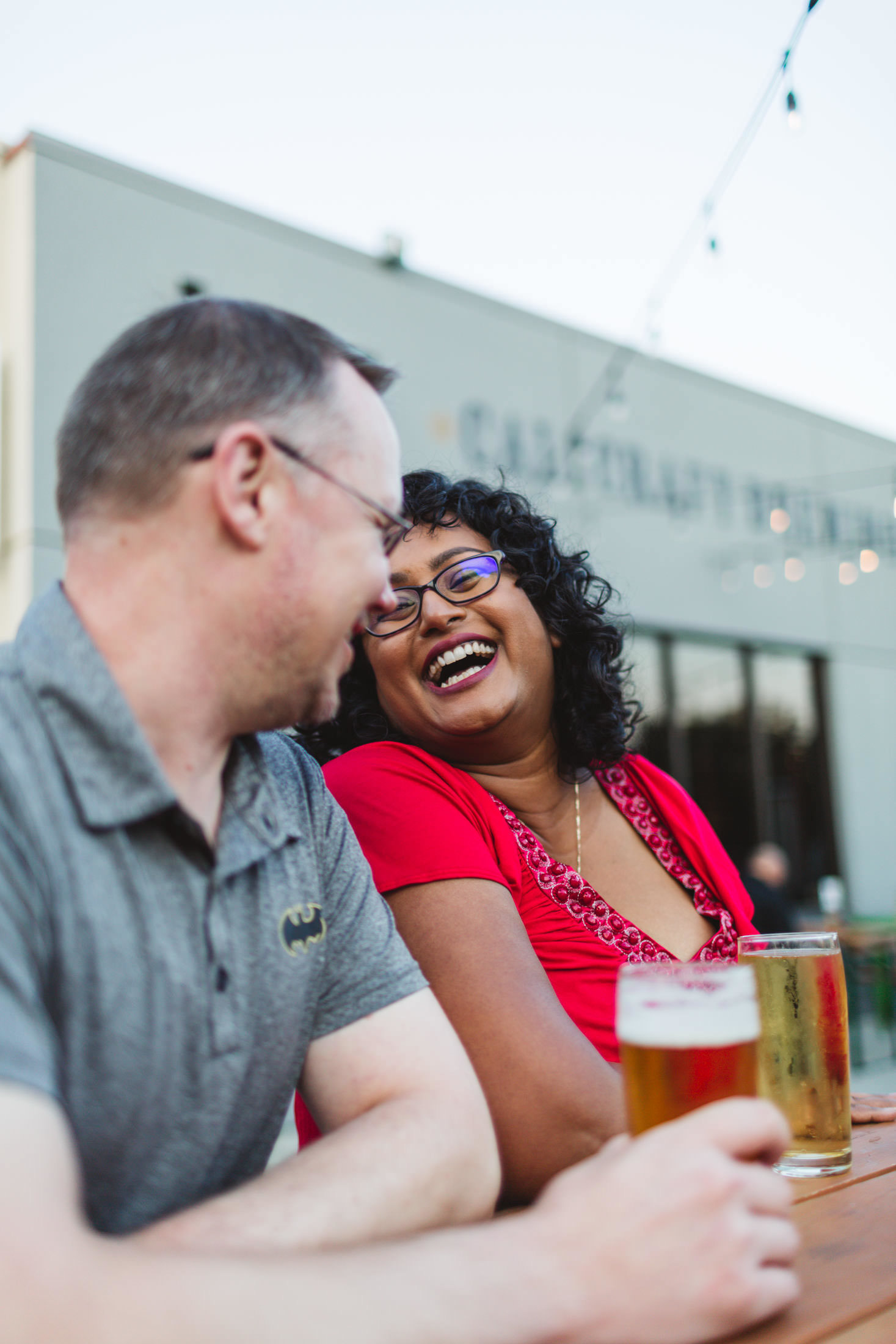 engagement couple sharing a beer and laughing at calicraft in walnut creek ca
