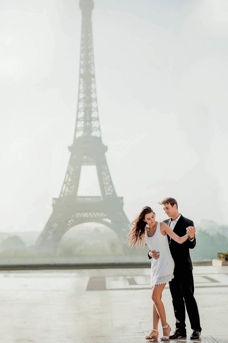 Bride and groom snuggle with the Eiffel Tower behind them, Paris, France
