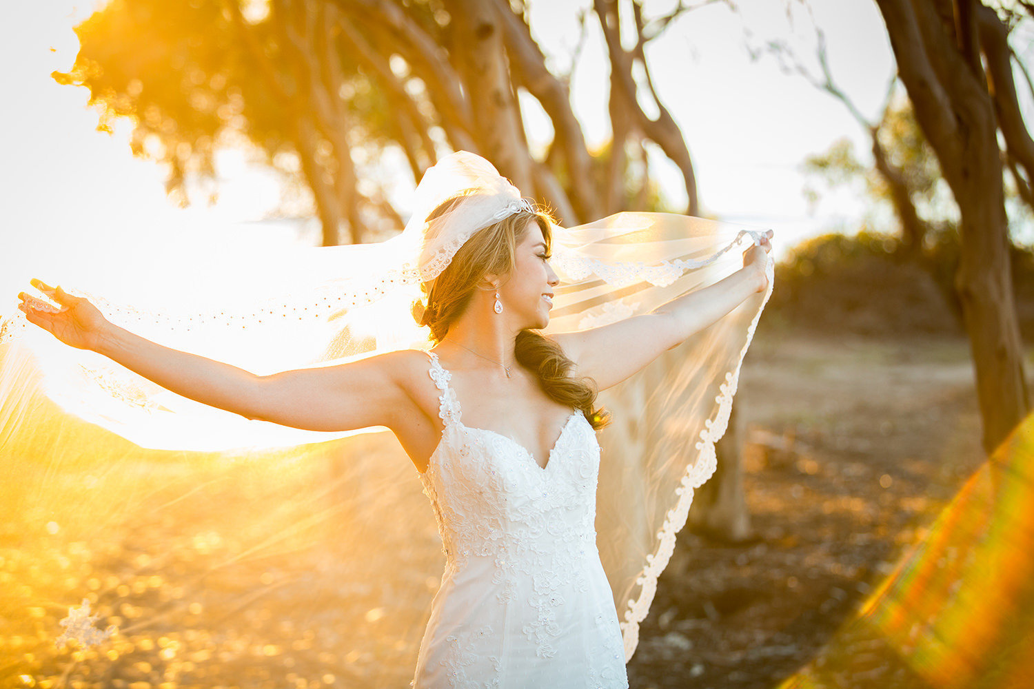 bride with long veil at sunset cliffs