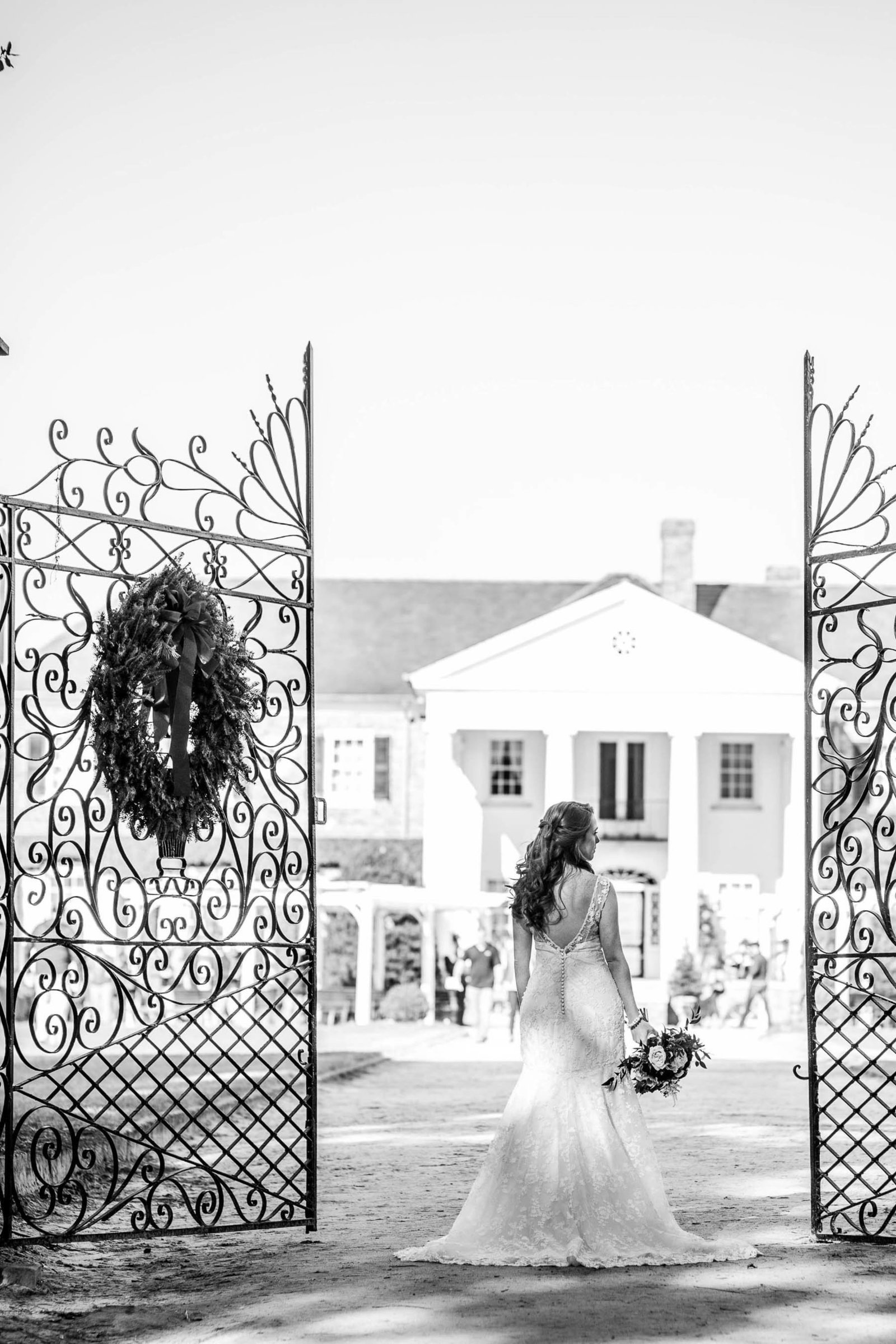Bride stands by gate of estate, Boone Hall Plantation, Charleston, South Carolina