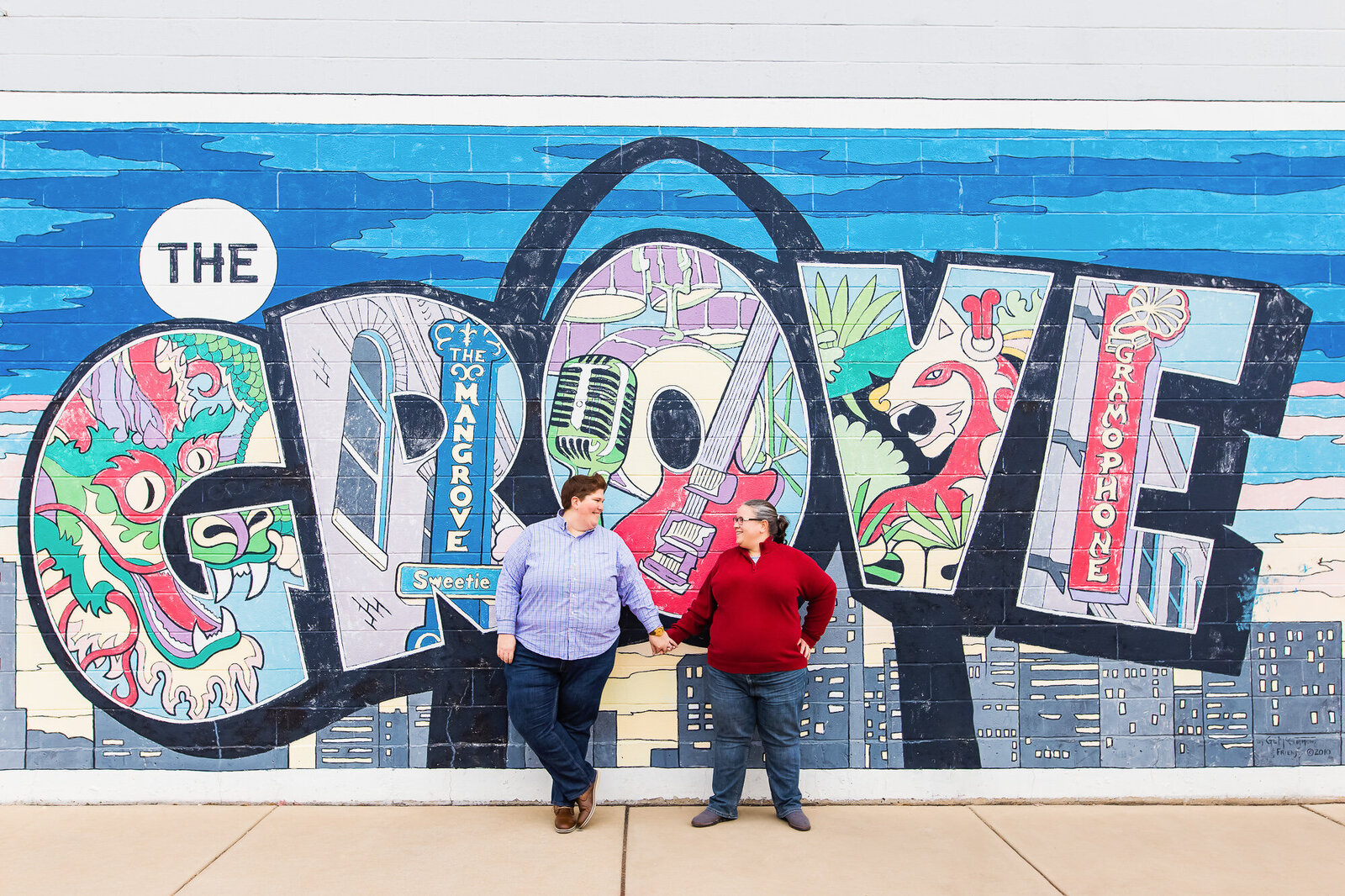 Same-sex couple holding hands in front of a mural in The Grove in Saint Louis