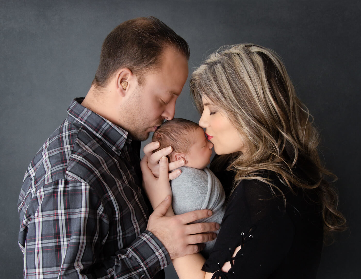 Newborn posed with parents in our Rochester, NY studio.