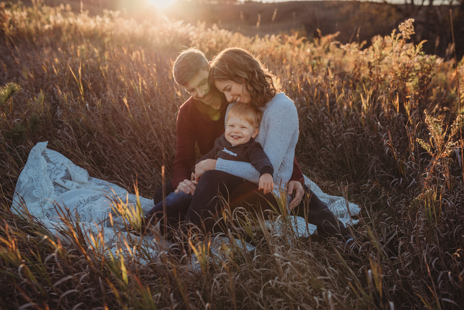 Parents hugging their young son in a field at sunset in Oshawa