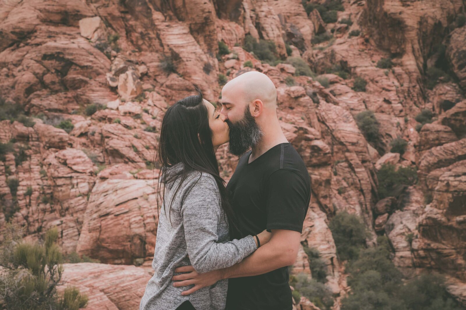 Couple kisses with red rocks in the background.