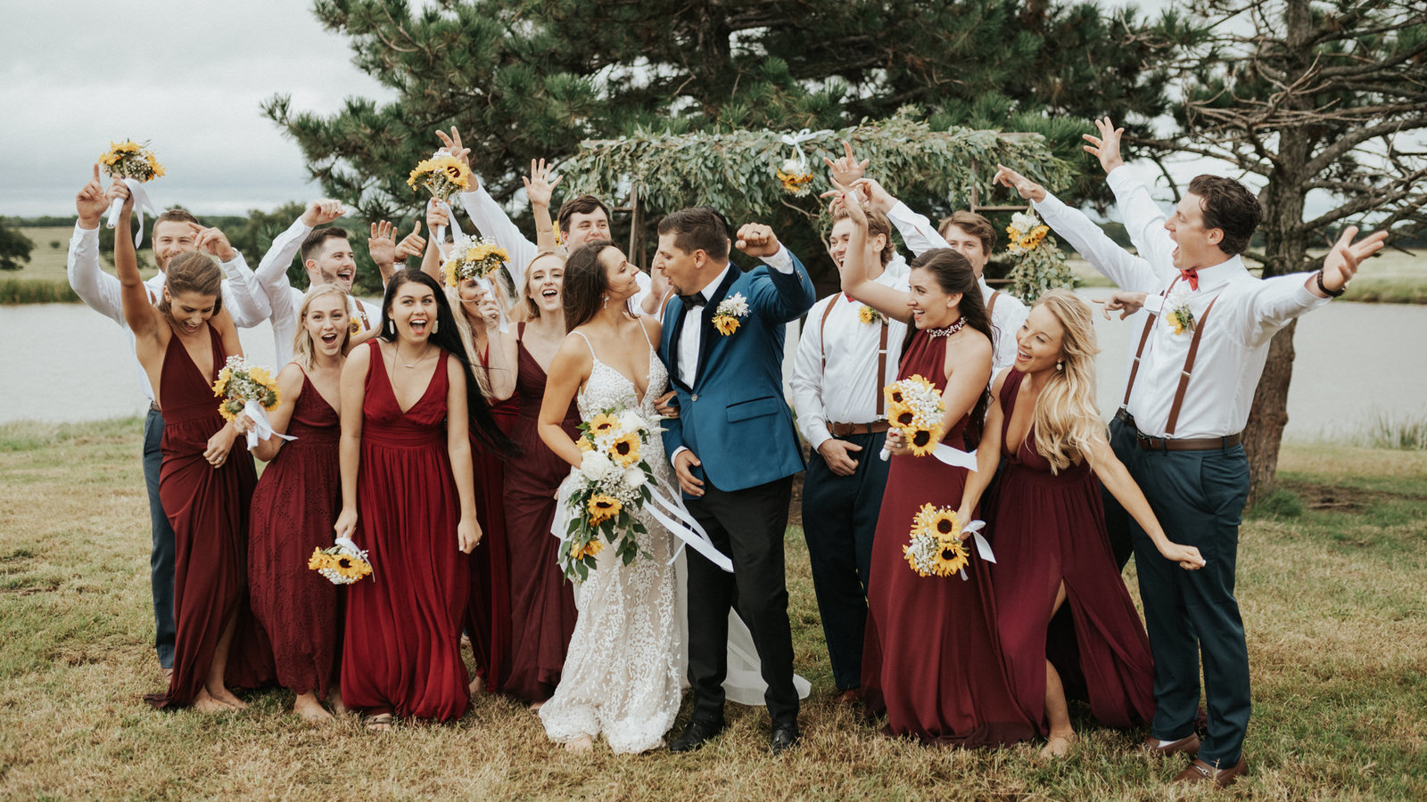 A bridal party cheering for the bride and groom at their backyard wedding.