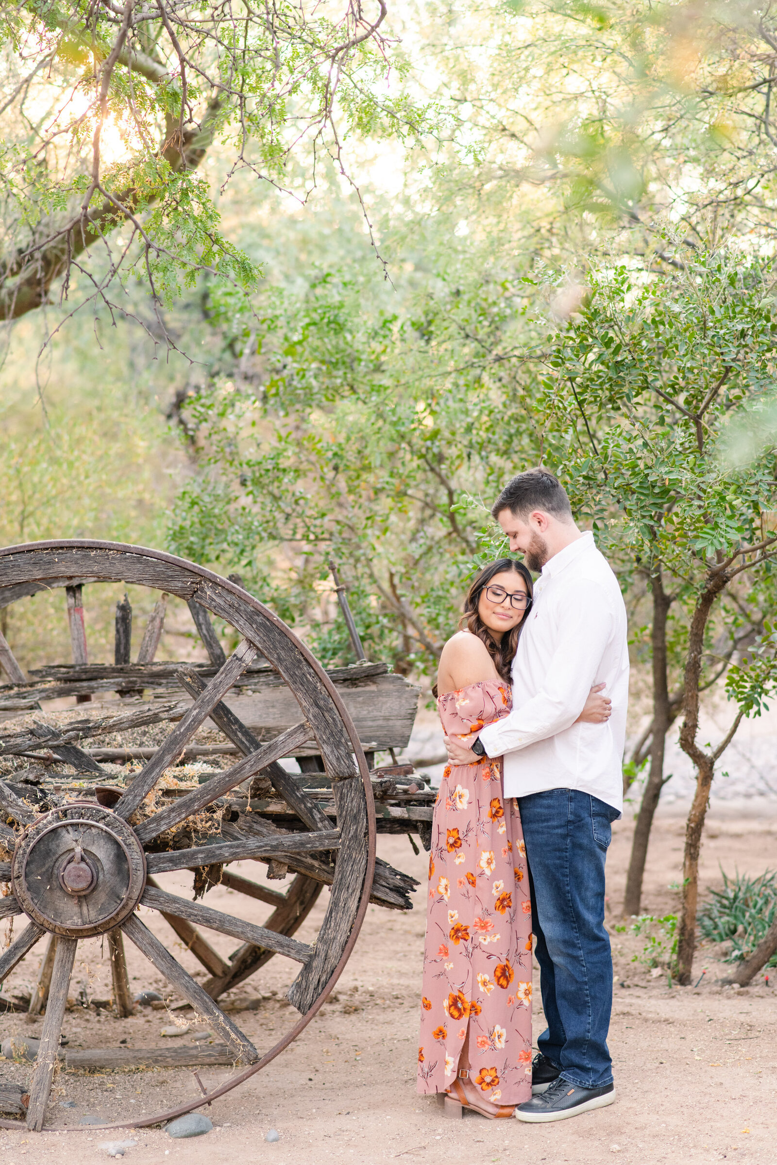 couple under mesquite tree by antique wagon wheel at Tucson estate
