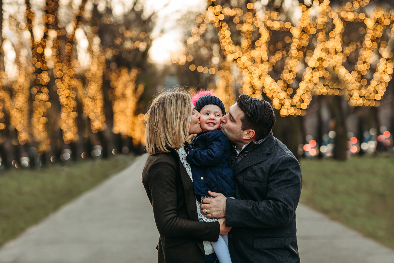 parents snuggle toddler outdoors by christmas lights in winter family session in boston