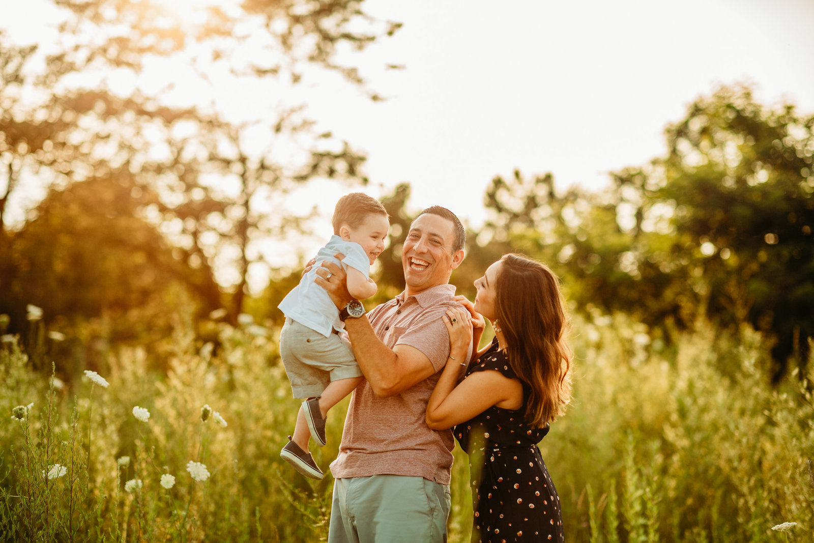 family with toddler boy laugh and hold him in air in sunset field in weymouth ma