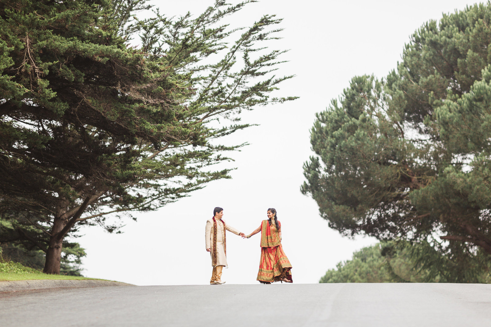 indian wedding couple framed by trees