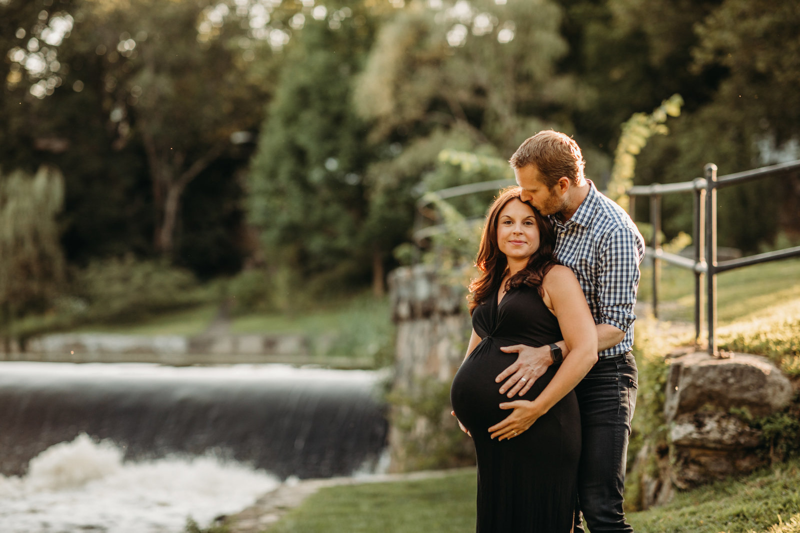 pregnant couple hugs and laughs beside a waterfall in natick ma