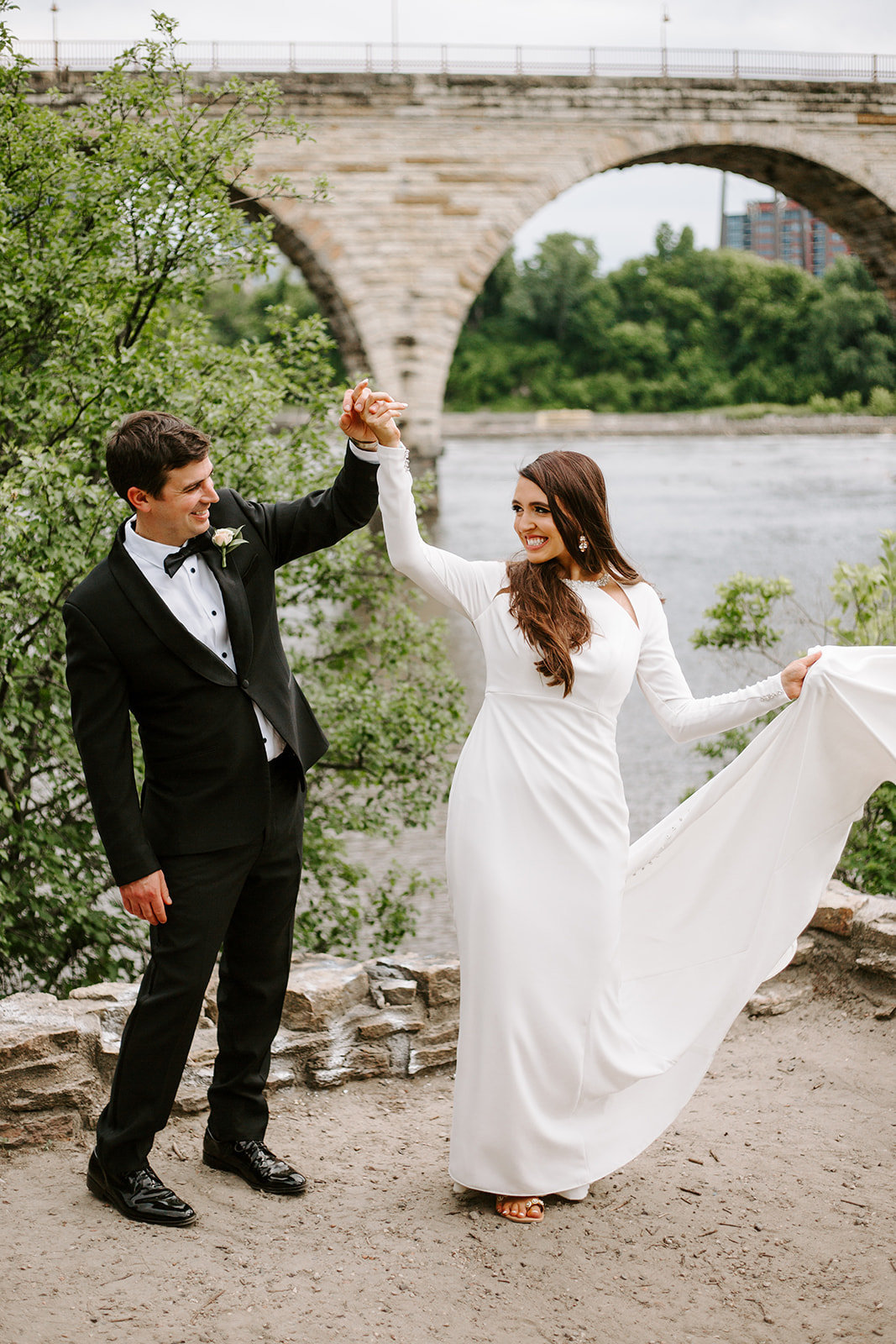 Bride throwing her wedding dress train in the air holding her husbands hand during their Minneapolis Wedding day