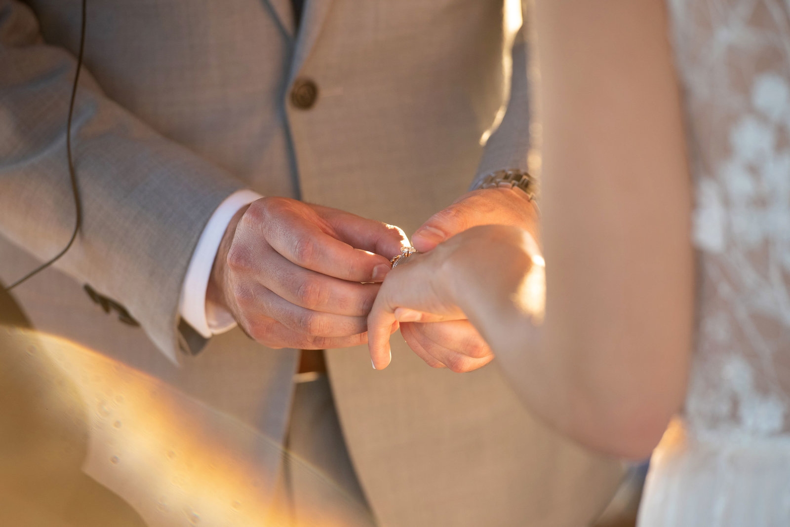 Groom putting ring on bride's finger at Atlantis Banquet and Events