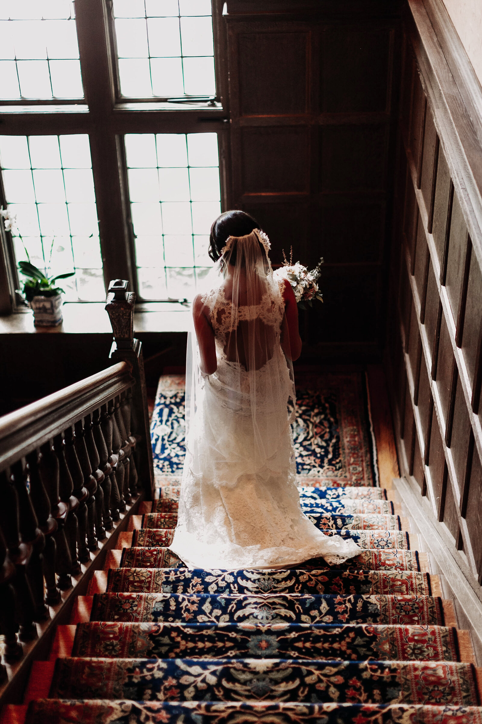 back of bride in lace dress in estate mansion