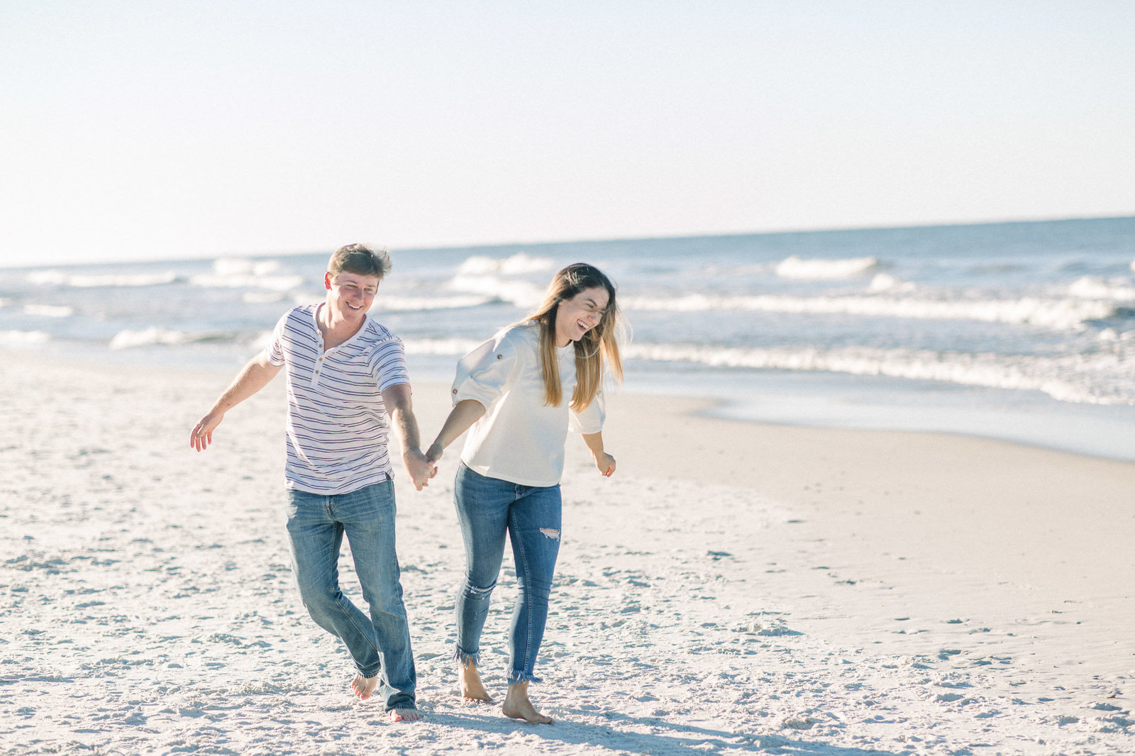 Laughing and running down the beach captured by Staci Addison Photography