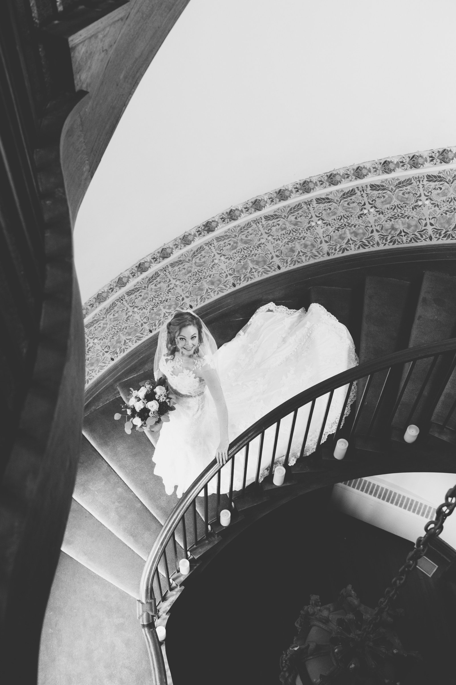black and white photo of bride walking down the stairs at Coindre Hall