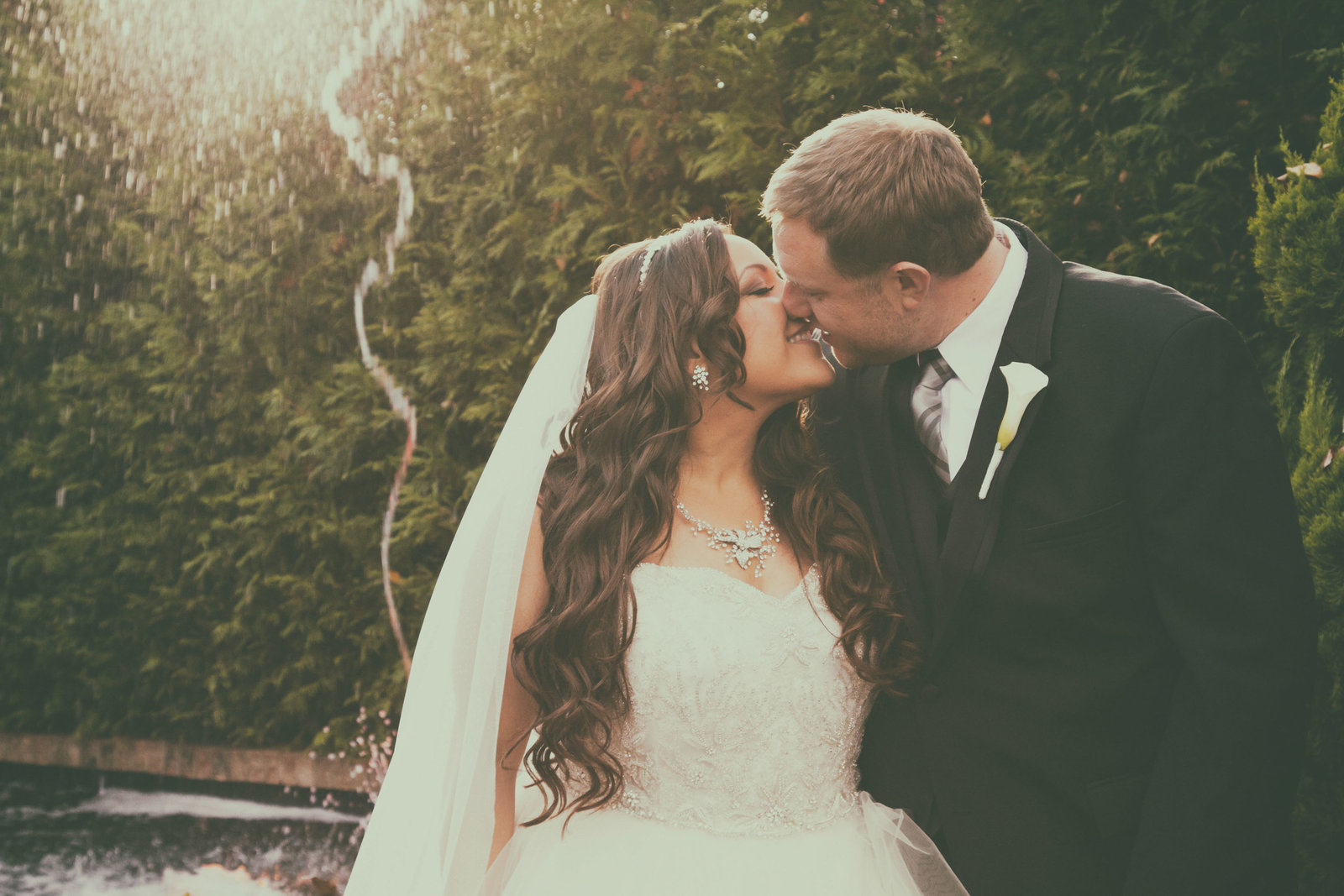 The bride and groom kiss with a fountain in the background.