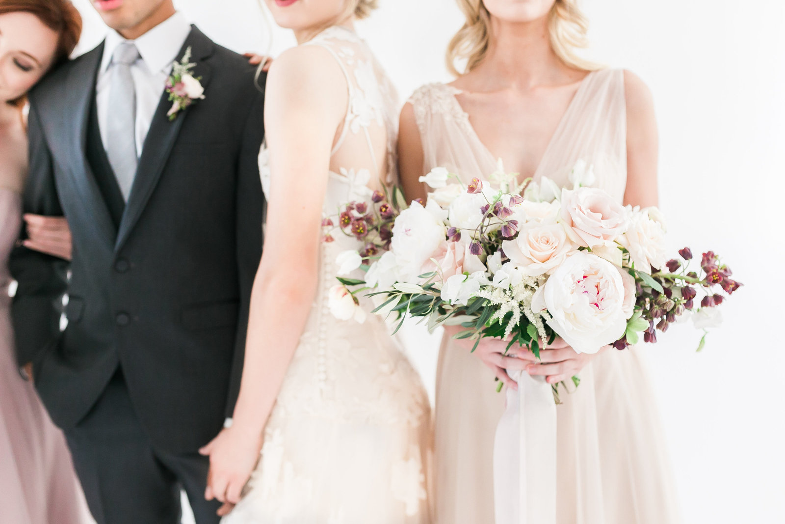 photo of a bride, groom and two bridesmaids in mauve and blush dresses with a bouquet of white, ivory, blush and eggplant