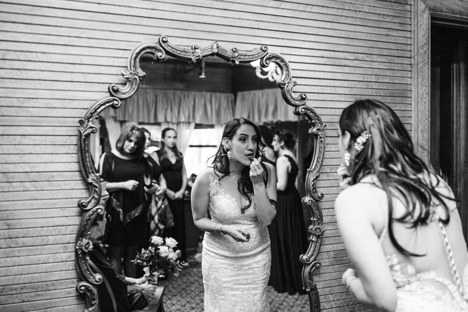 bride looks into mirror and applies lipstick on wedding day in boston ma