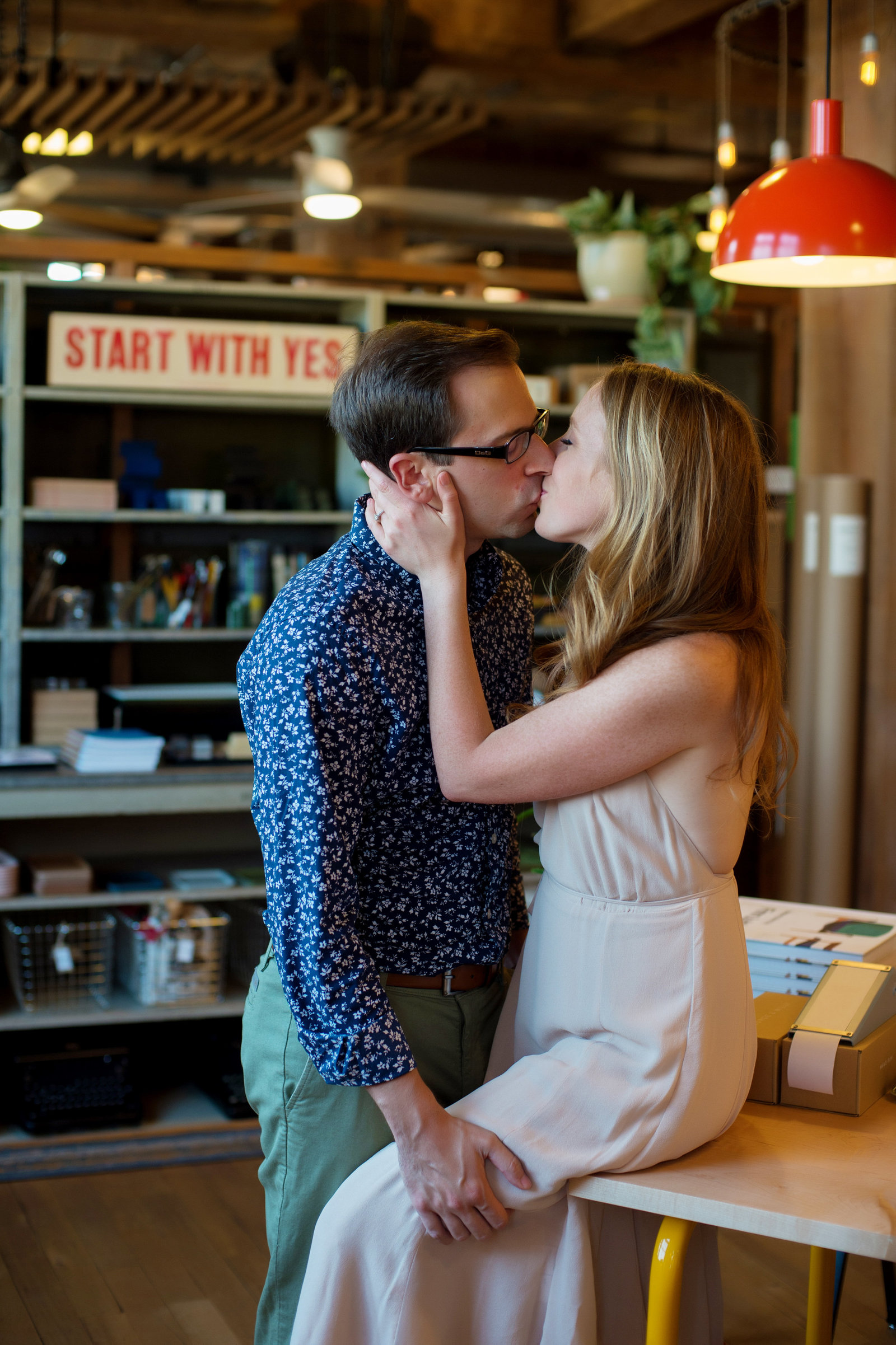an engaged couple kiss in schoolhouse electric