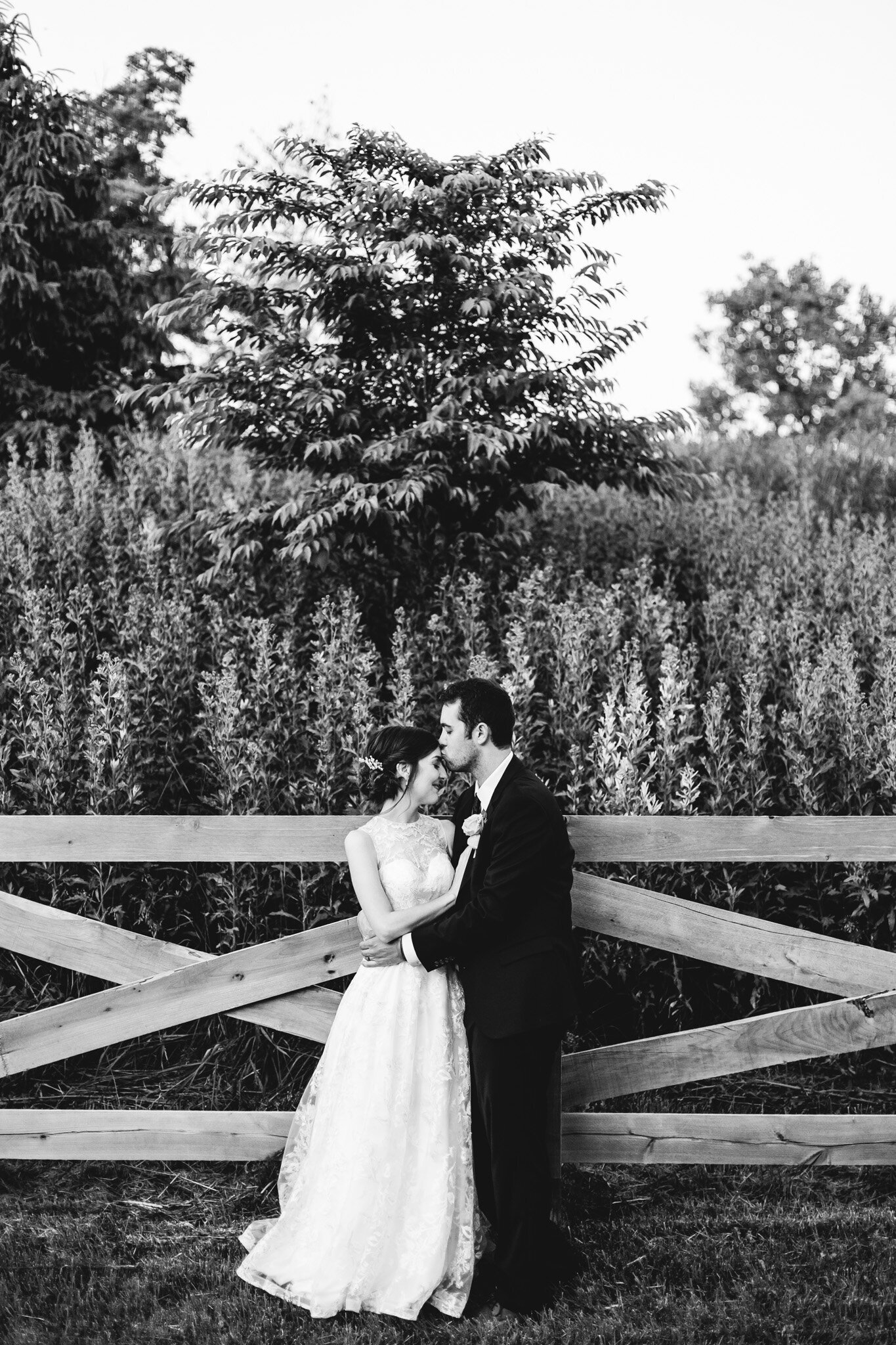 bride and groom embrace along a fence ohio wedding