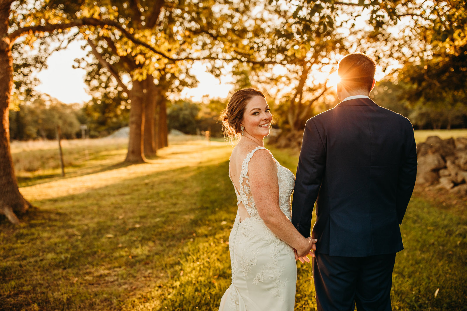 bride peeks over her shoulder during sunset couples portraits