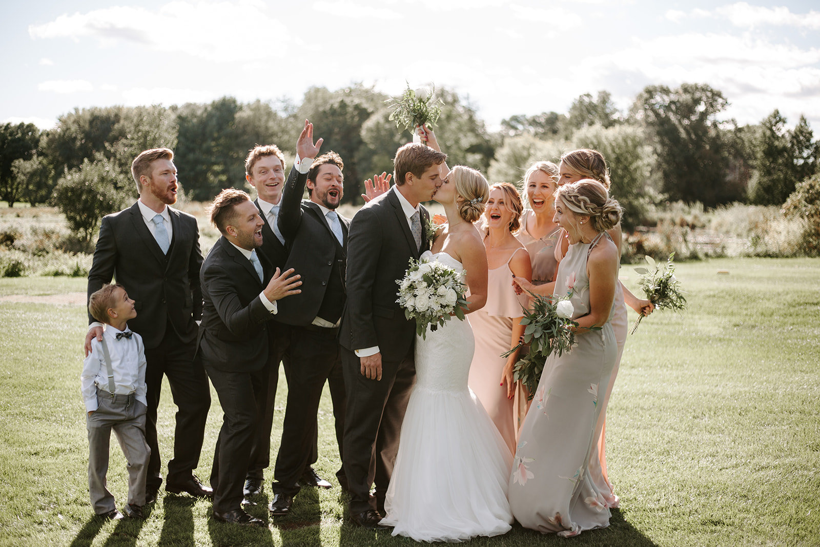 Bride and groom kissing with their bridal party cheering behind them during their Minneapolis Wedding