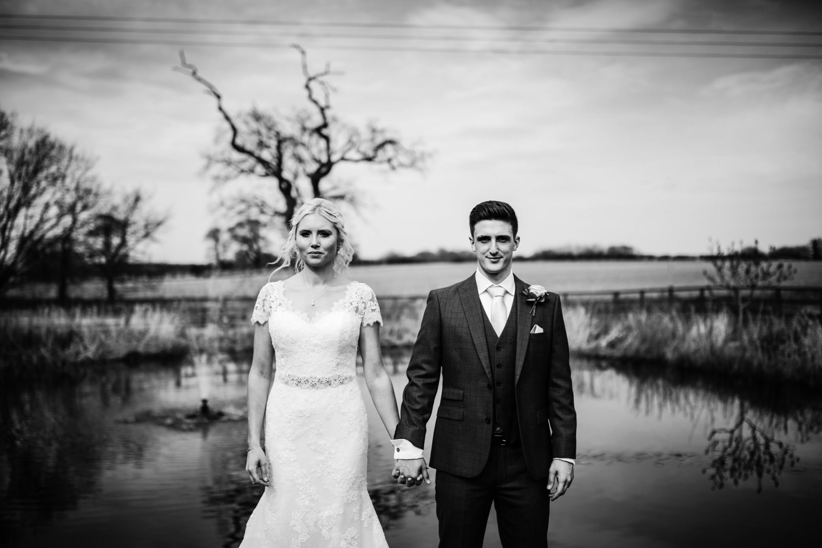 A black and white portrait of a smiling Bride and groom holding hands in front of a pond at a Norfolk barn wedding venue.
