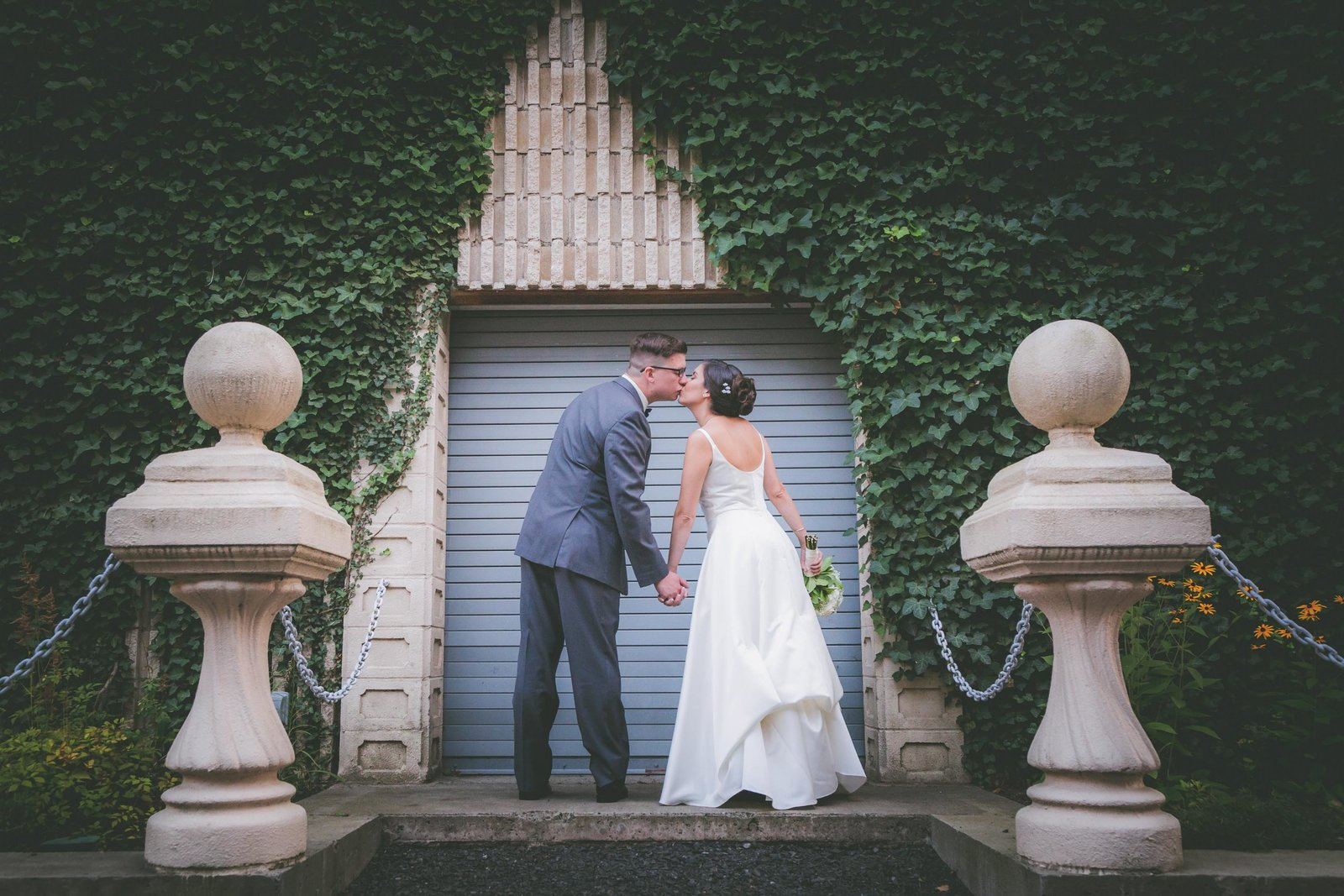 Connecticut bride and groom kiss with columns and ivy surrounding them.
