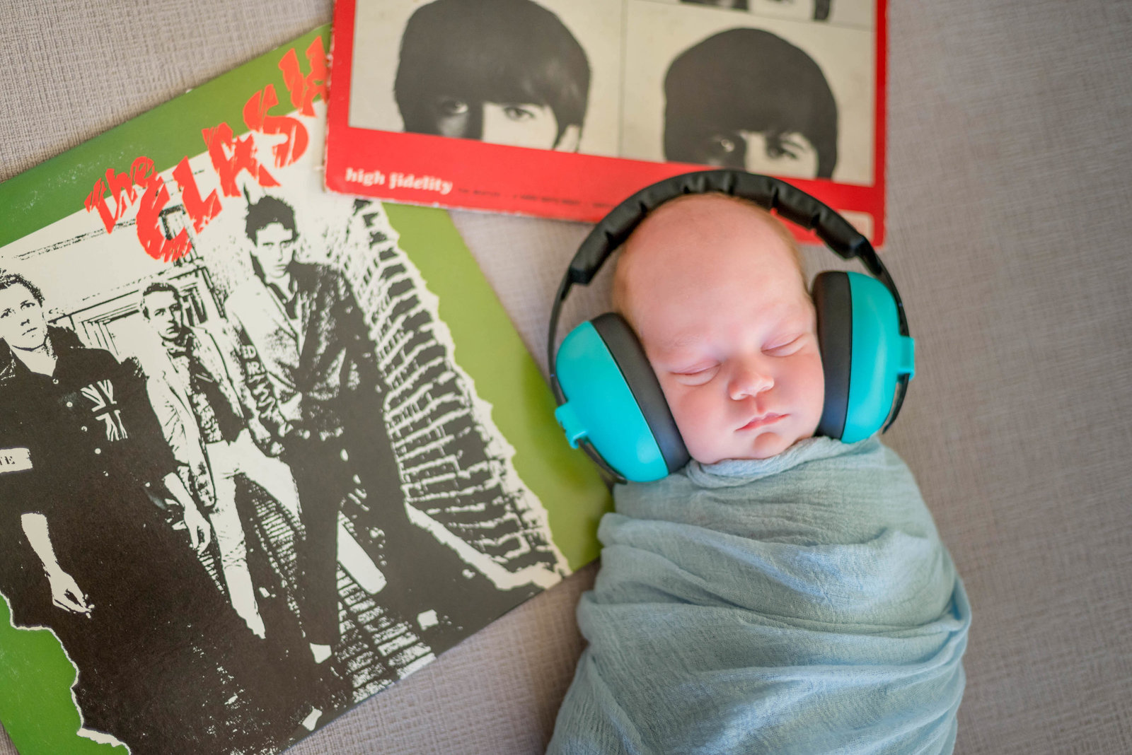 Newborn posed at home on furniture in lifestyle session Boston listening to music headphones on