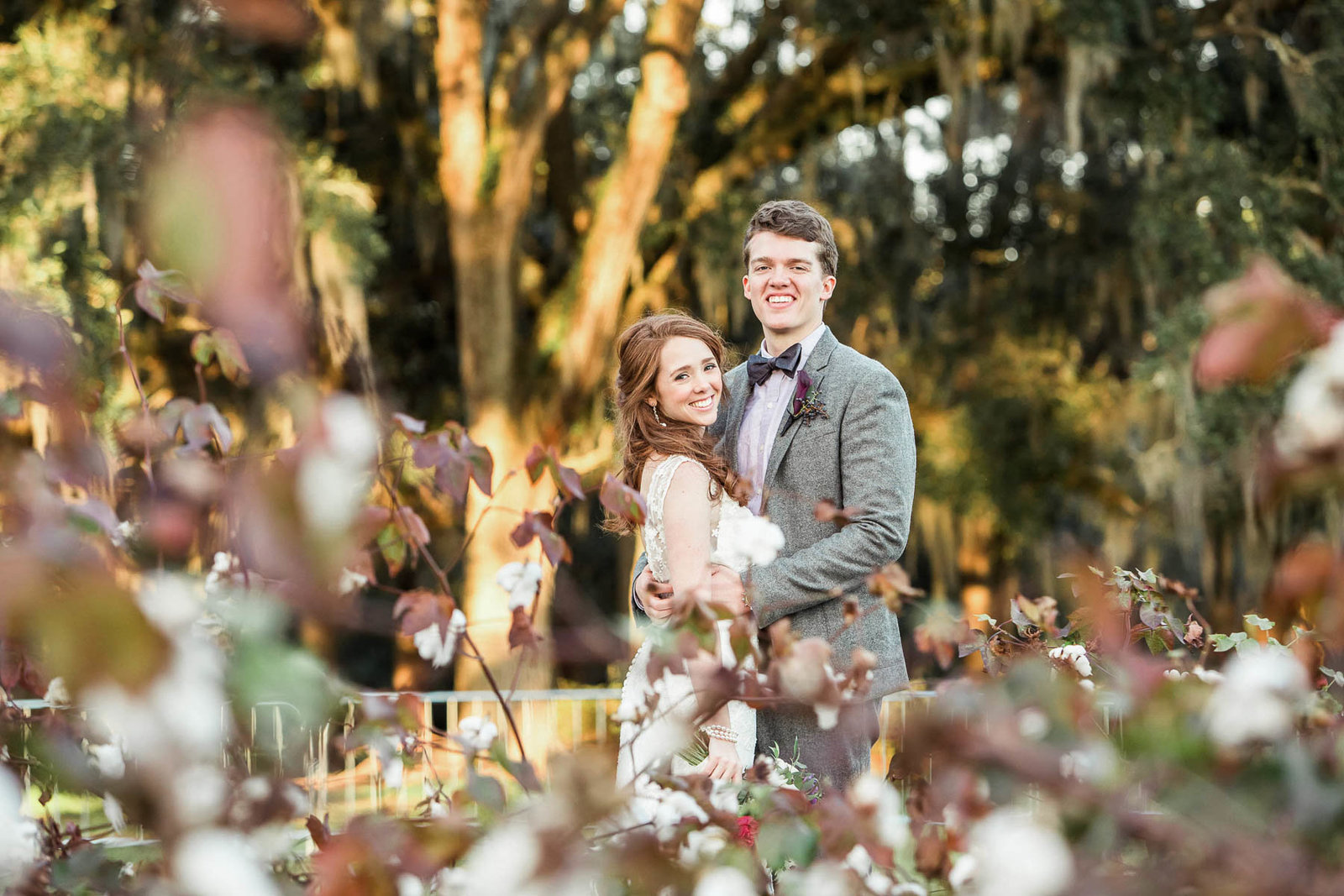 Bride and groom stand in cotton field, Boone Hall Plantation, Charleston, South Carolina