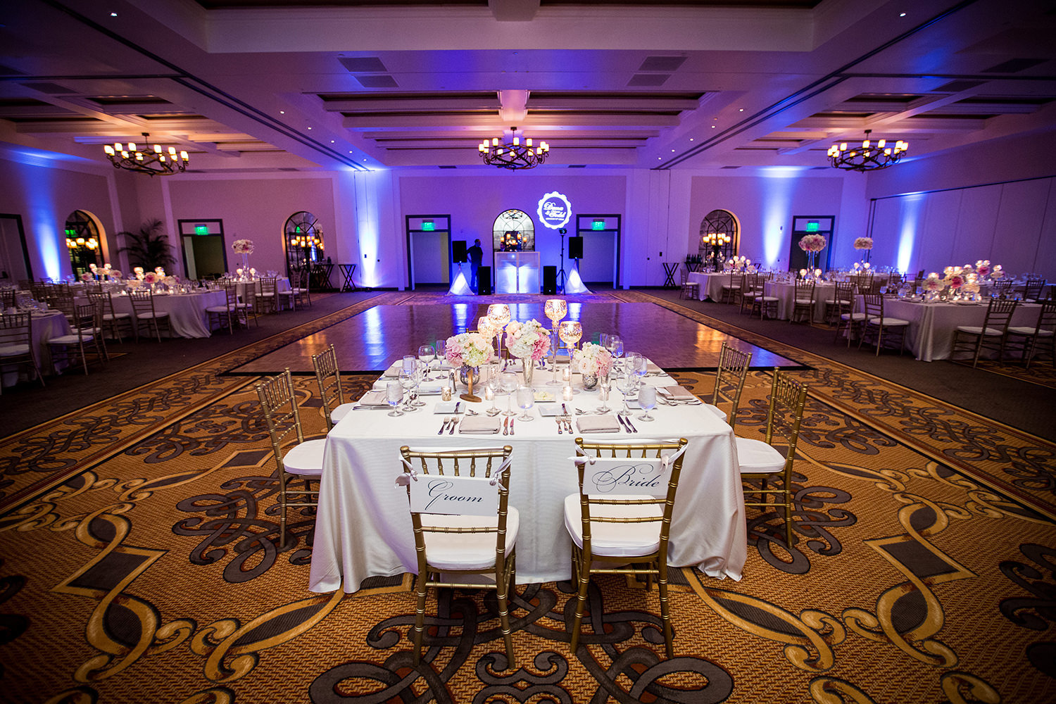 The Bride and Grooms wedding head table at their reception.  Purple uplighting