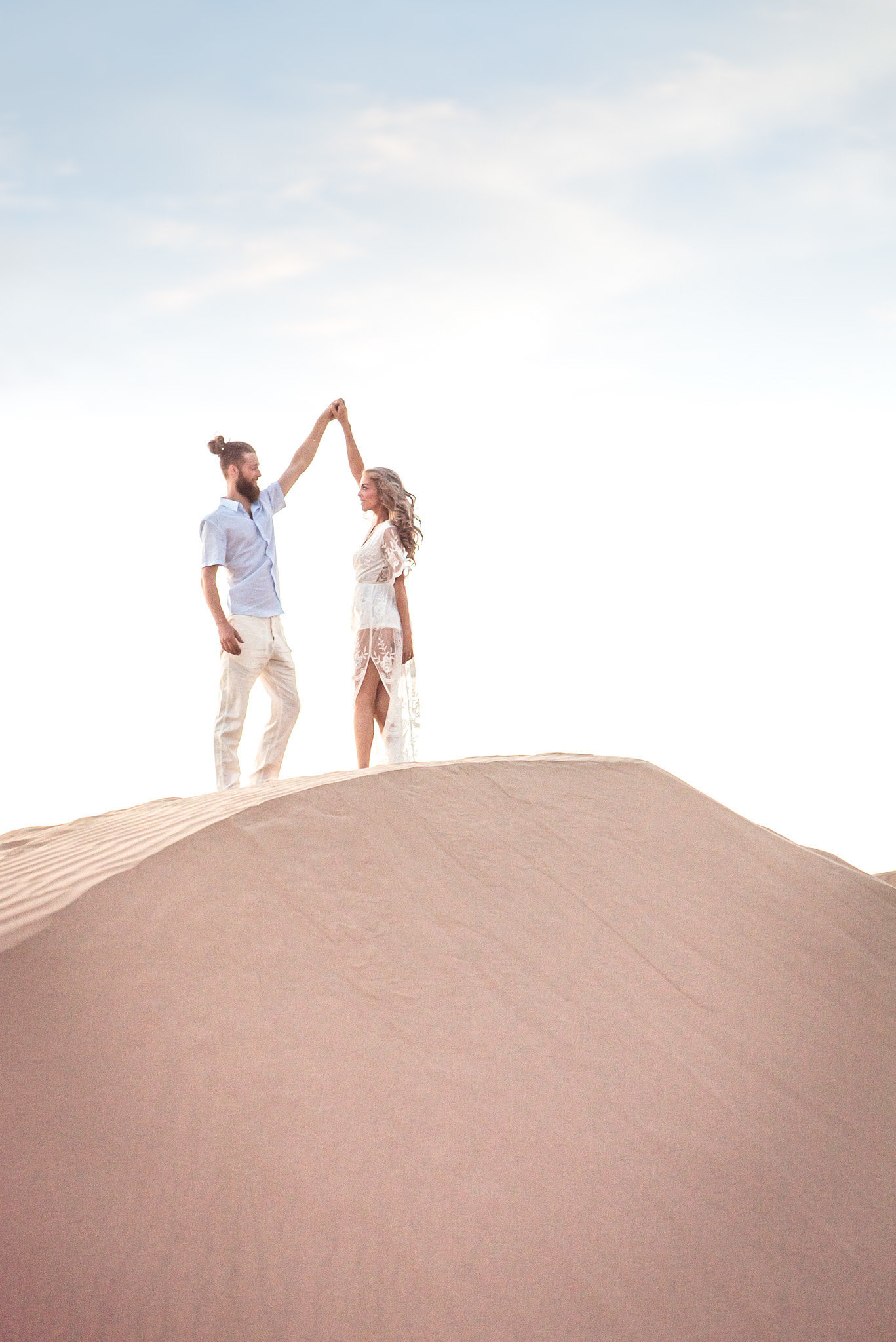 Glamis Sand Dunes Boho Engagement Session Photo of Engaged Couple Dancing on a Sand Dune | Tucson Wedding Photographer | West End Photography