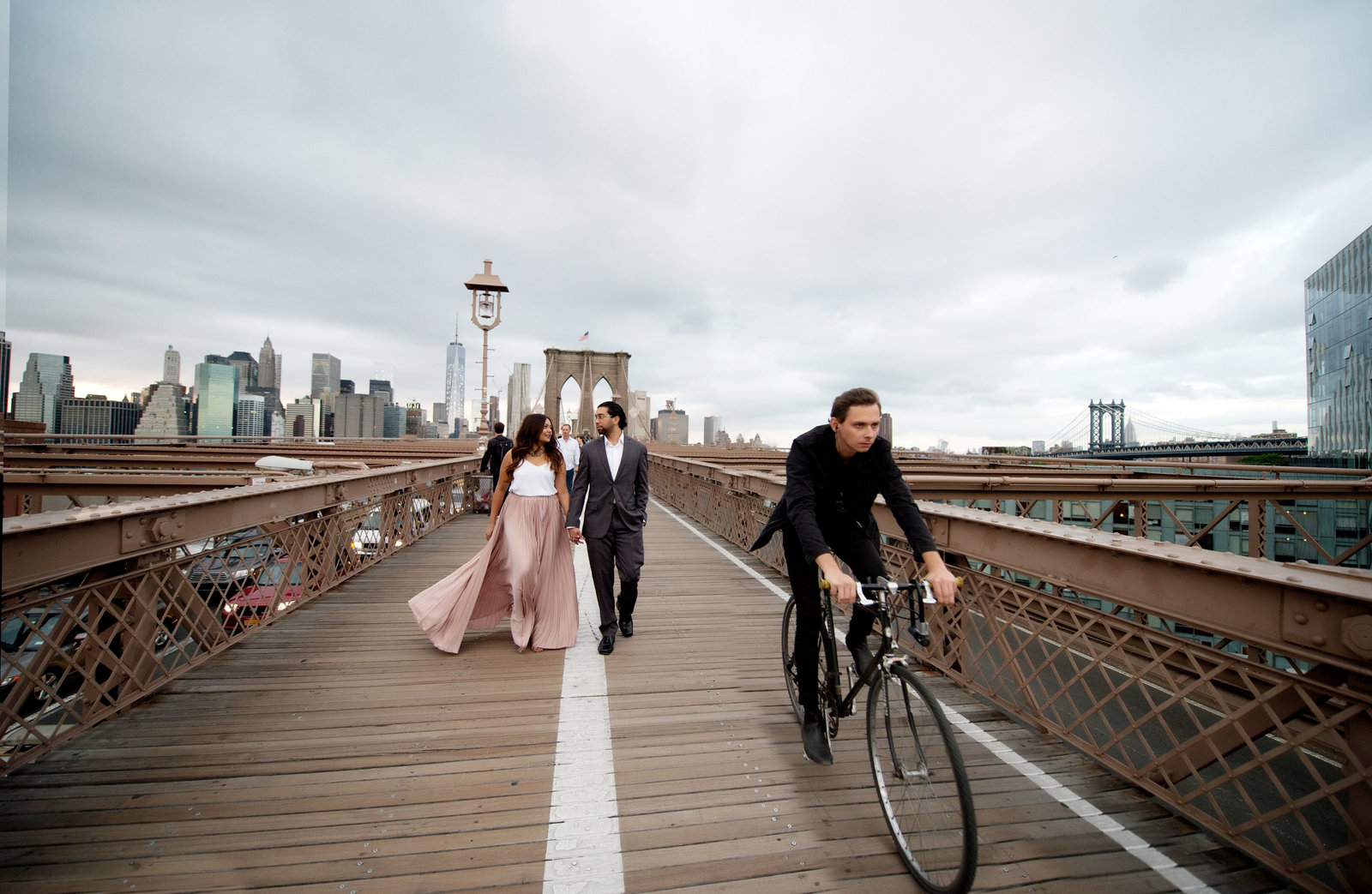an engaged  couple kiss on the brooklyn bridge as a biker pedals past