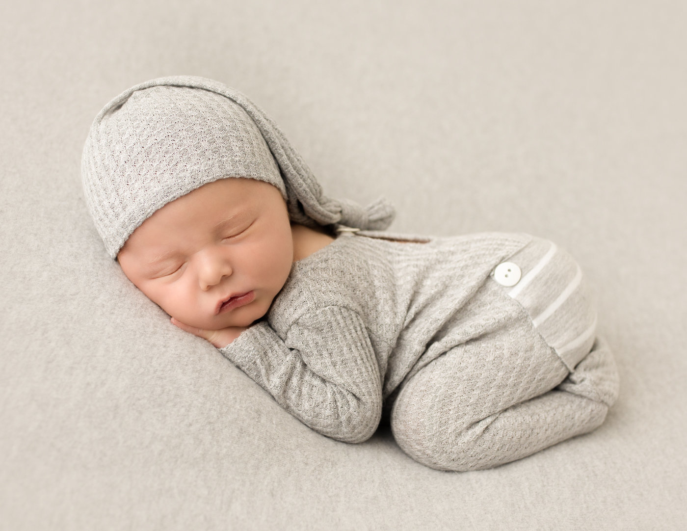 Sleepy newborn boy posed in our Rochester, Ny studio.