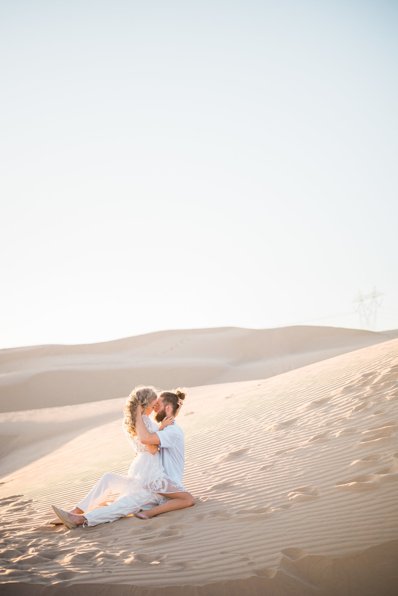 Glamis Sand Dunes Boho Engagement Session Photo of Couple Sitting in Sand | Tucson Wedding Photographer | West End Photography