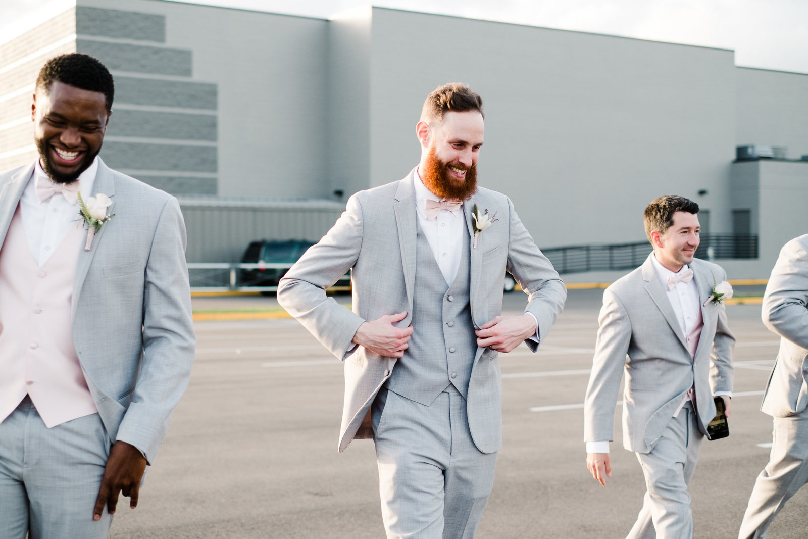 Groom and groomsmen walking together and laughing at wedding in Orlando, FL