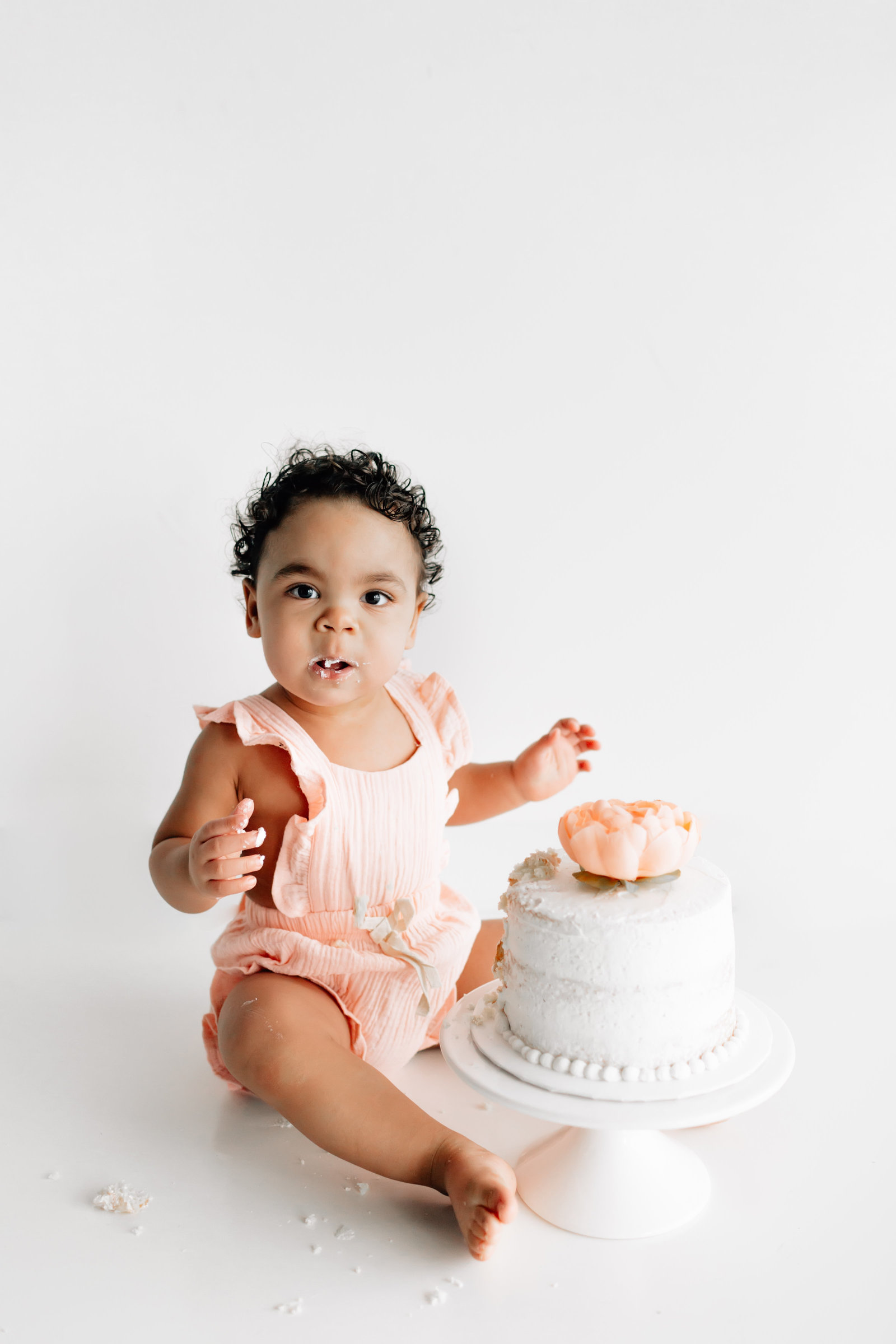 First birthday cake smash session in studio, milestone session, baby in pink outfit, white cake, white studio