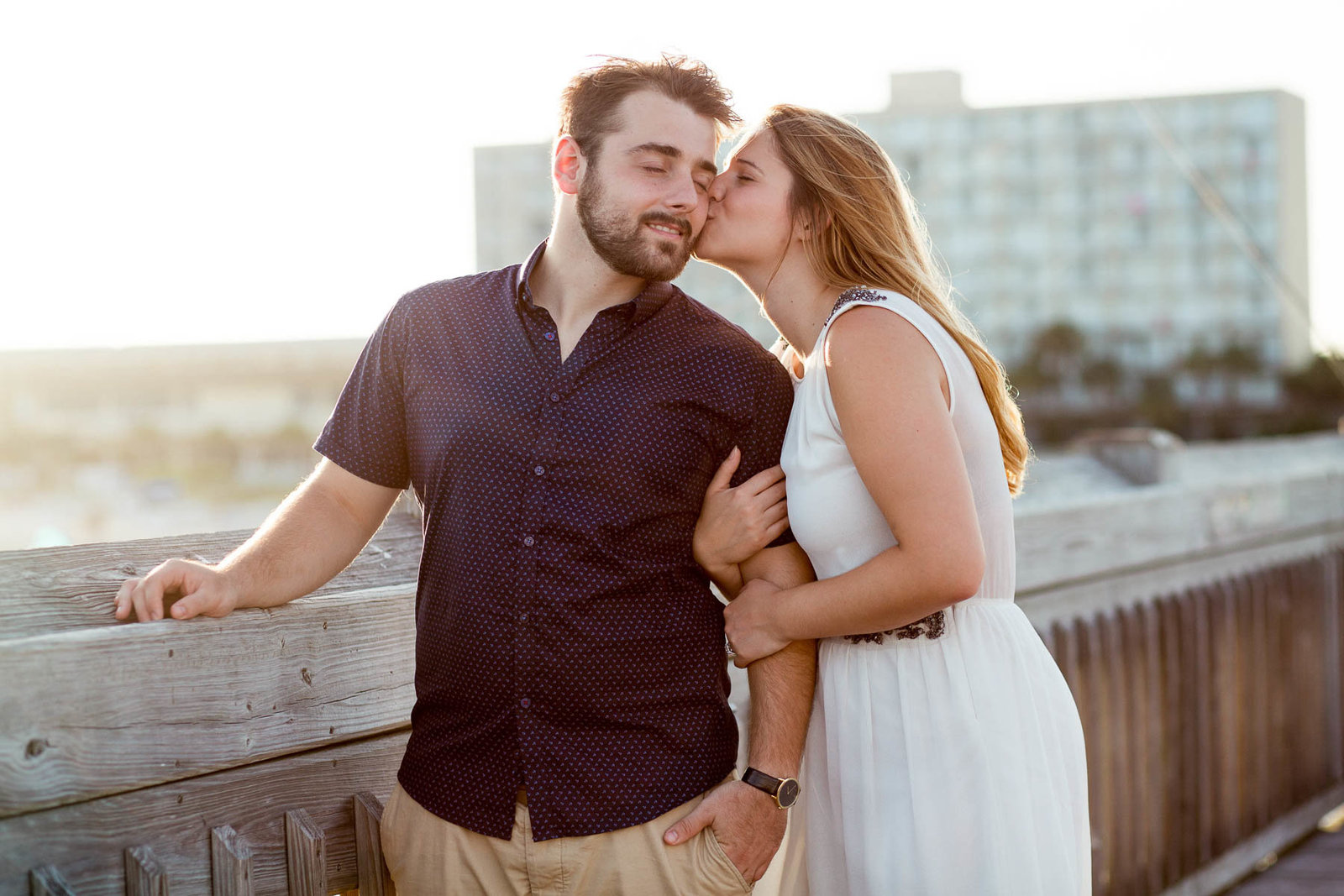 Engaged Couple kiss at sunset on pier, Folly beach in Charleston, South Carolina