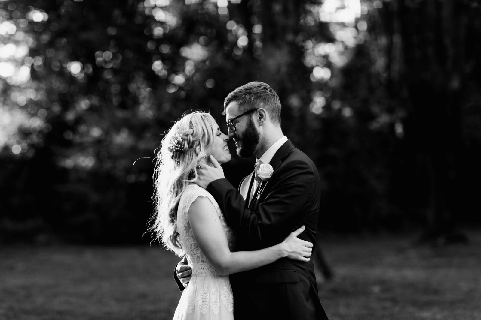 black and white bride groom kissing sunset