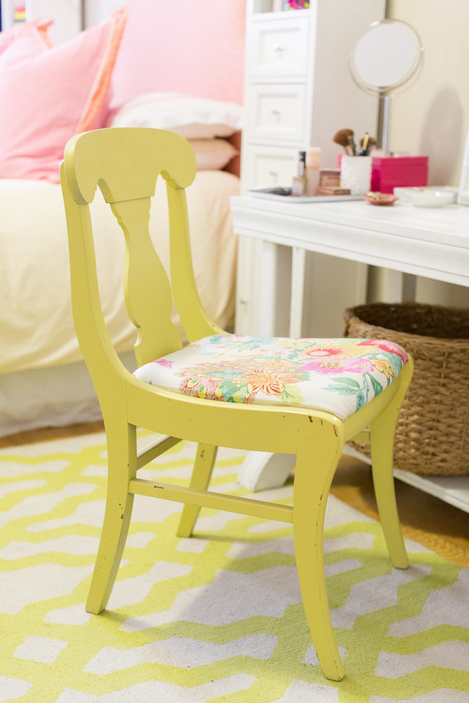 A yellow chair with flower upholstery in front of a vanity.