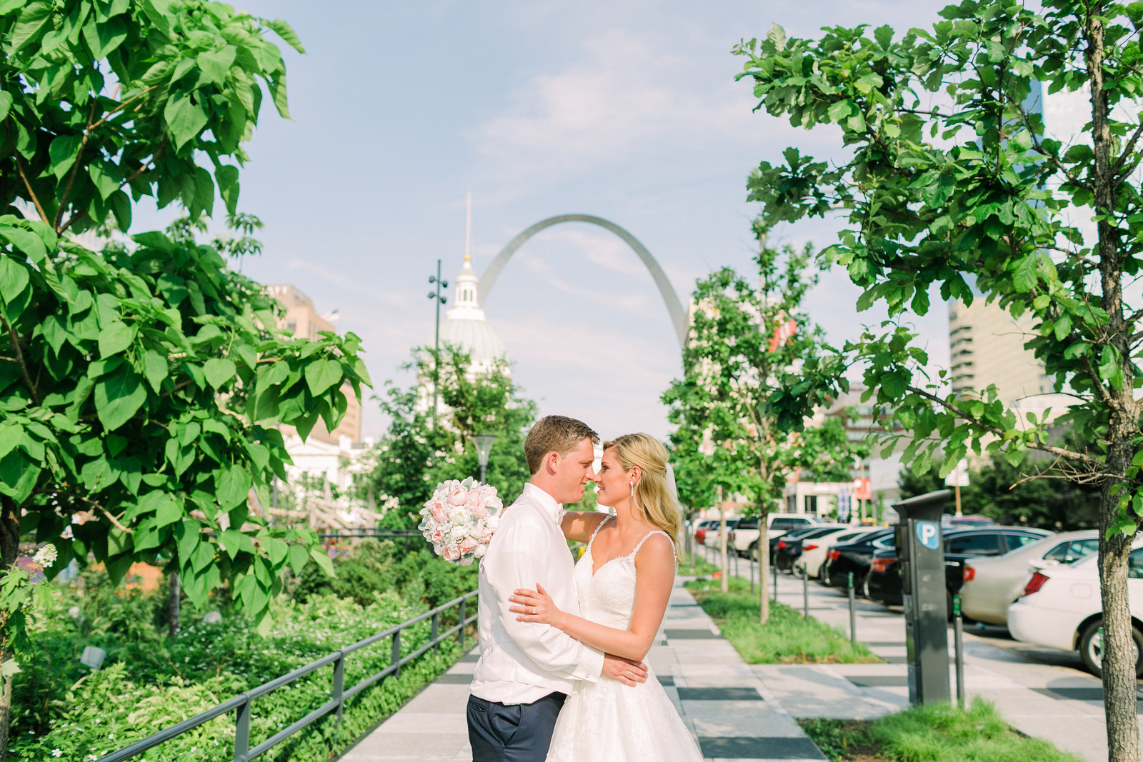Bride and Groom, Molly and Marcus, embrace on the sidewalk of Kiener Plaza with the St. Louis Arch in the background.