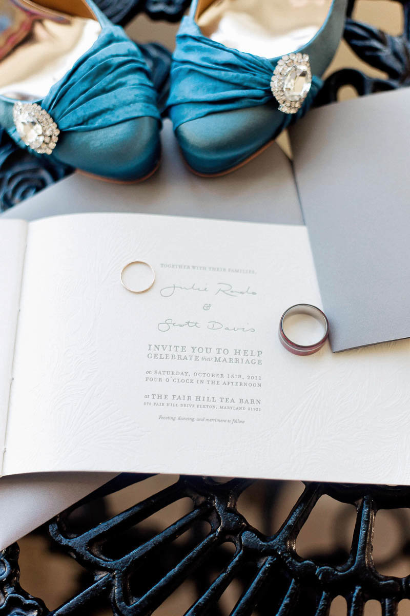 Letterpress Invitation suite is surrounded by wedding bands and blue shoes, Fair Hill Tea Barn, Elkton, Maryland. Kate Timbers Photography.