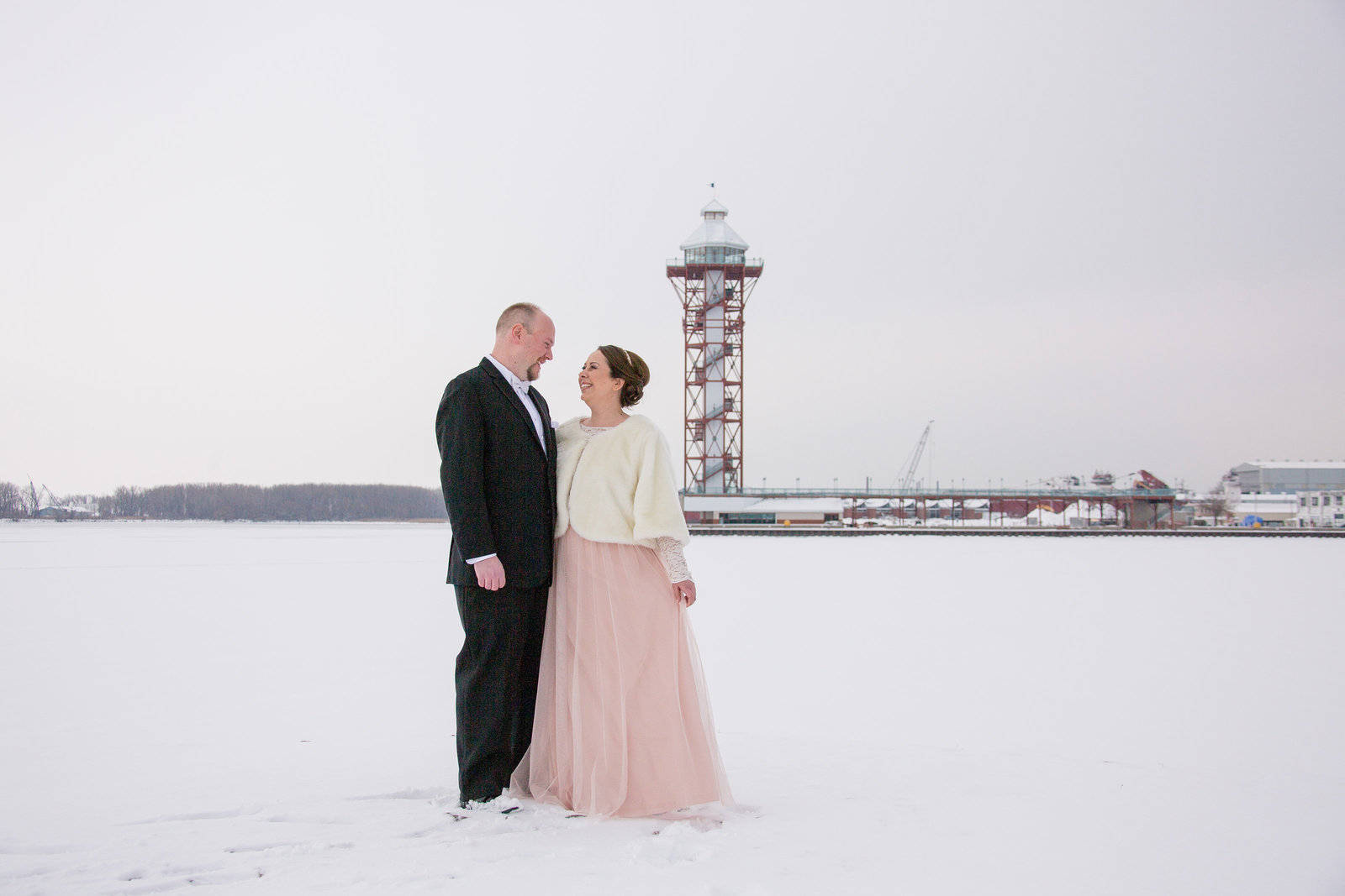 Bride and groom pose outside Sheraton Erie Bayfront Hotel in winter with the Bicentennial Tower in the background