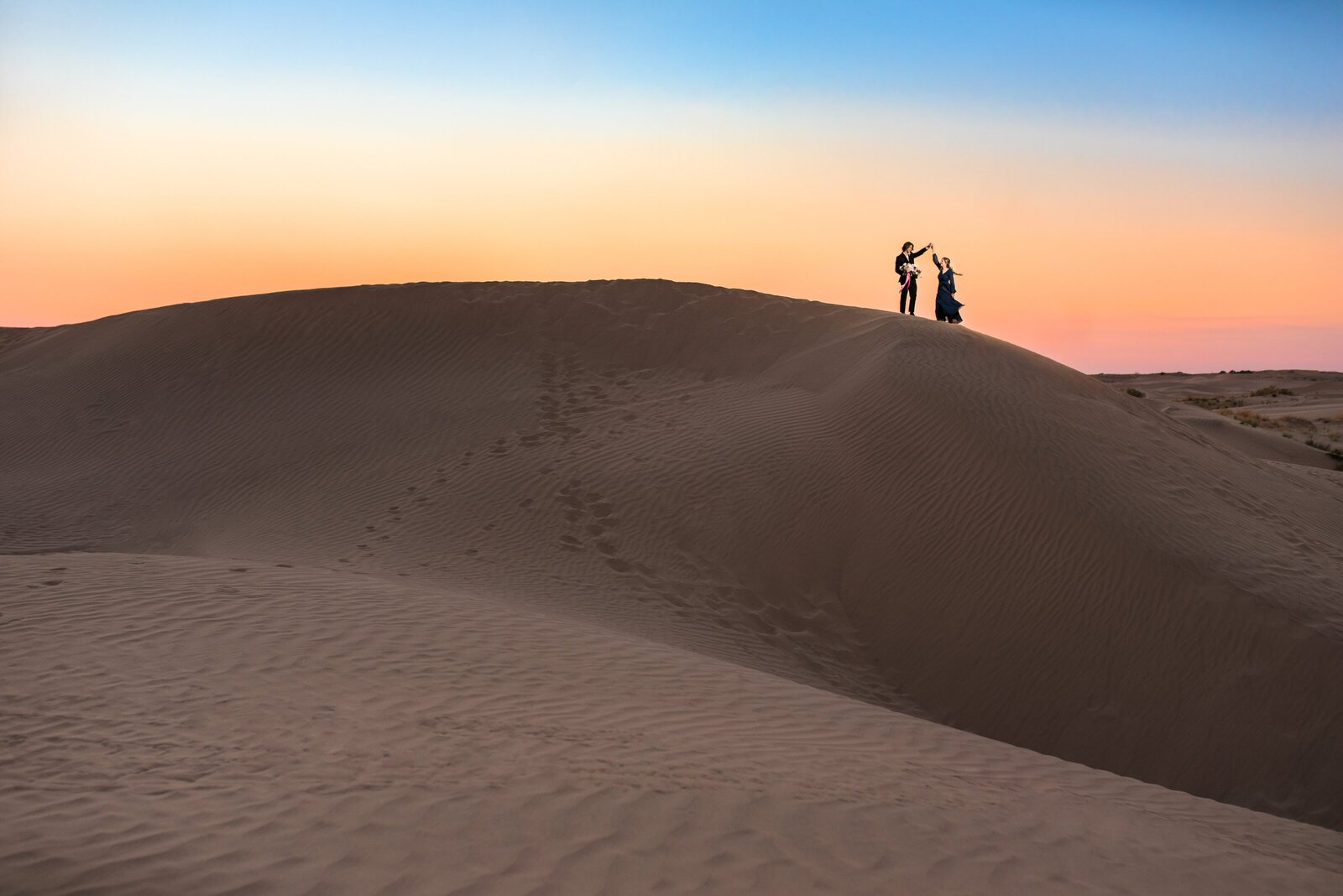 Engagement session couple on top of a sand dune at Little Sahara at sunset