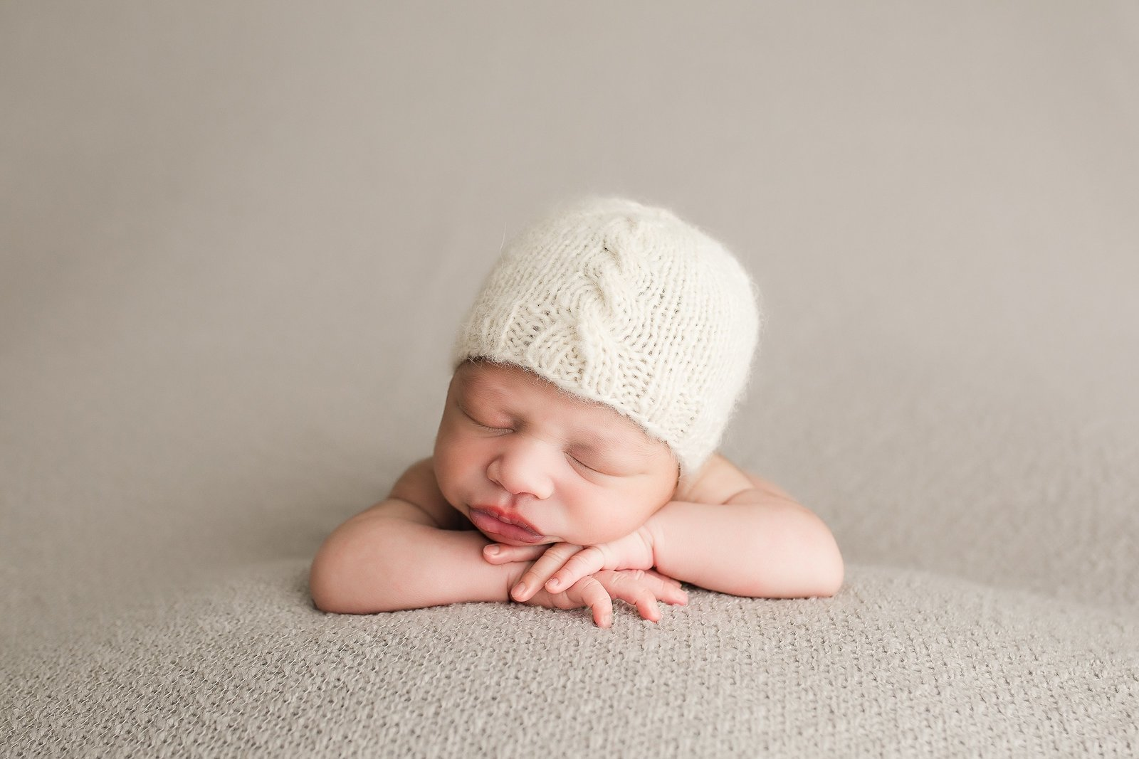 Newborn boy with cream hat