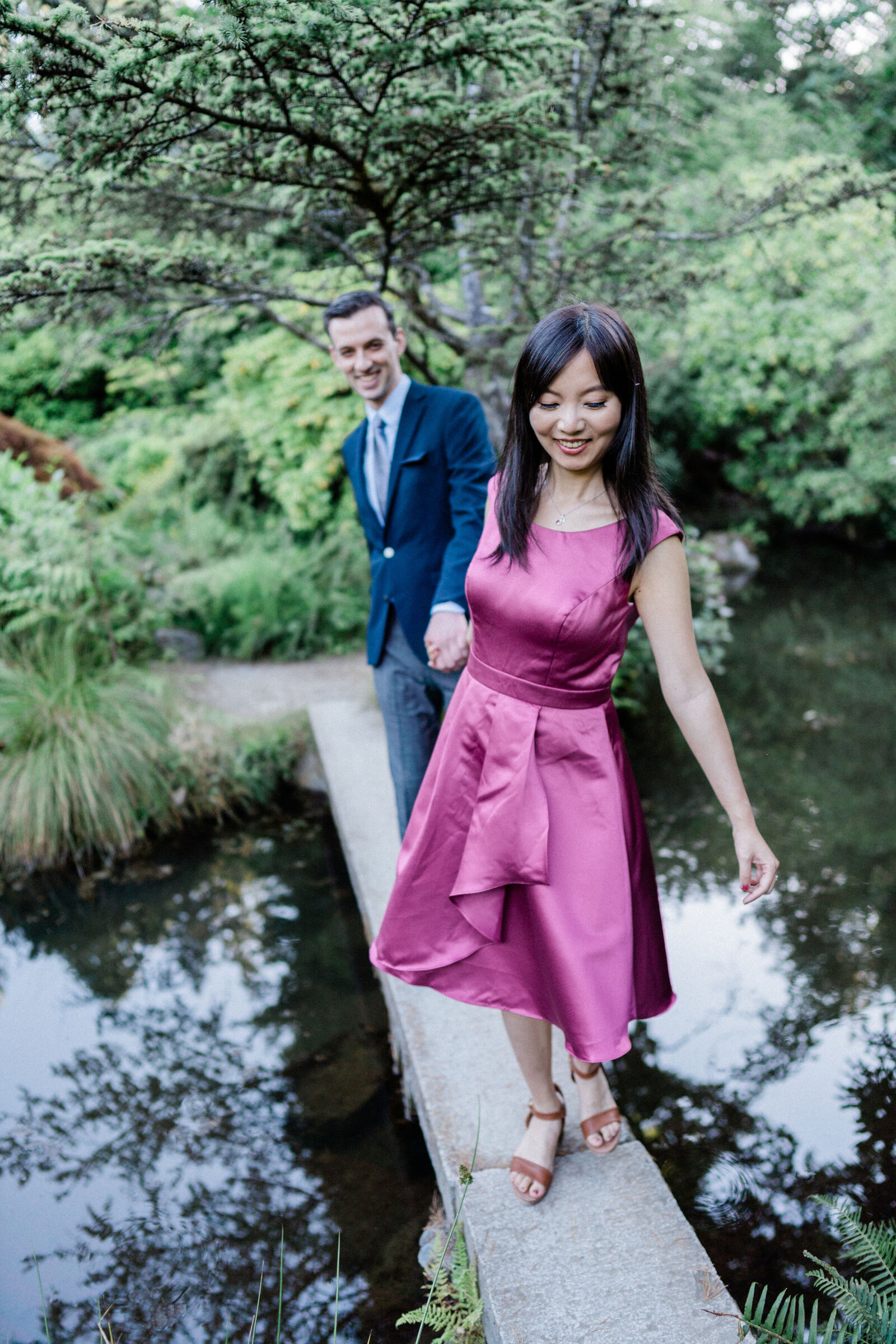Wife leads husband across pond at Japanese garden Kubota Garden, the best spot for romantic engagement photos in Seattle