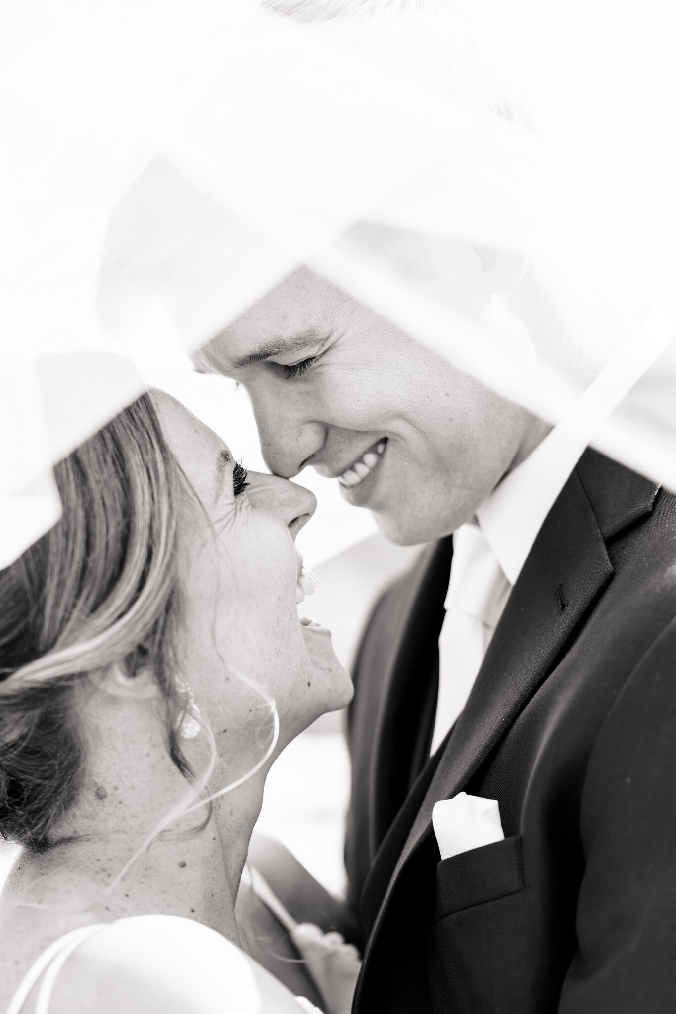 Black and white photo of bride and groom with noses touching